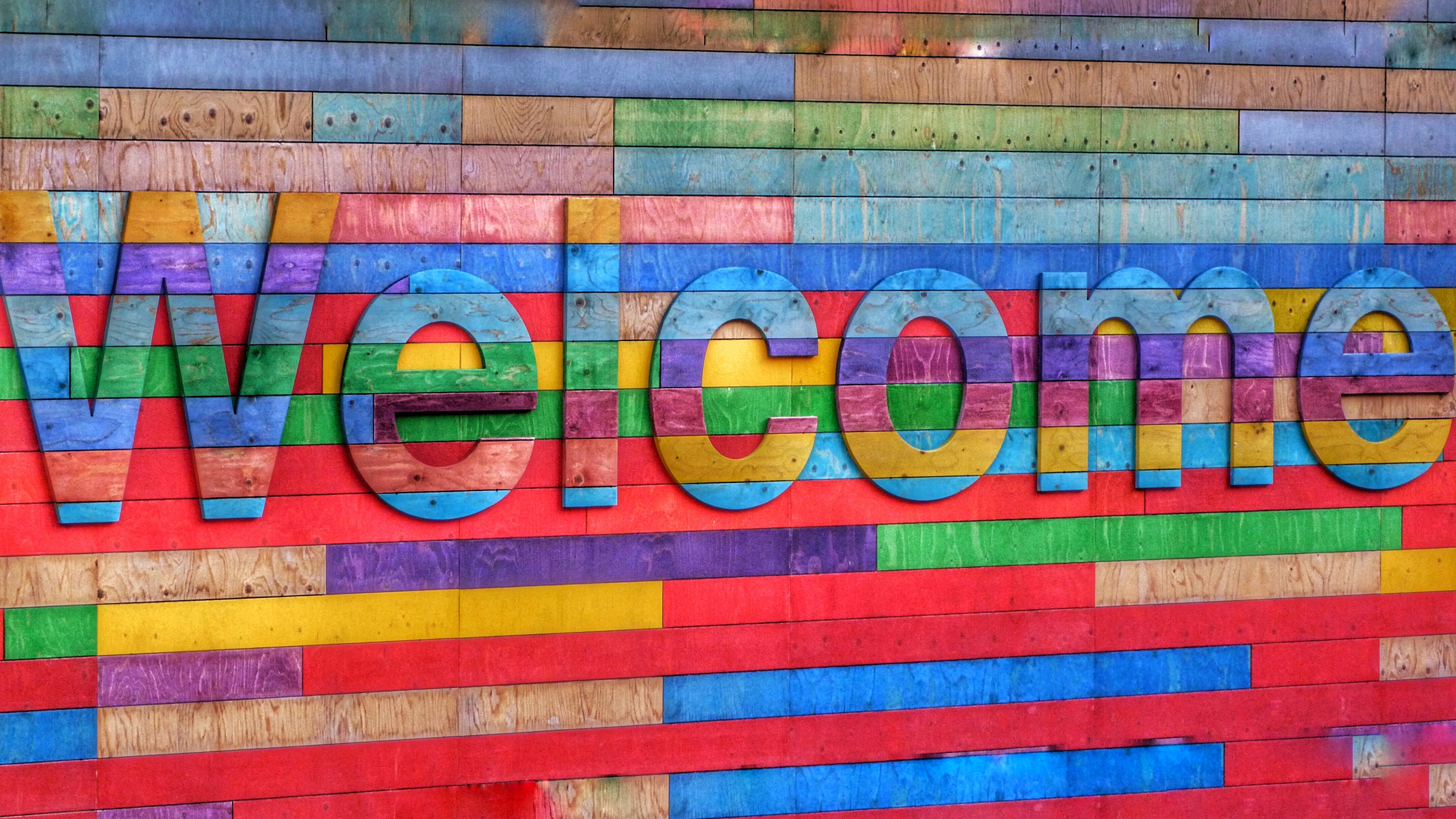 Brightly coloured word welcome written in wood.