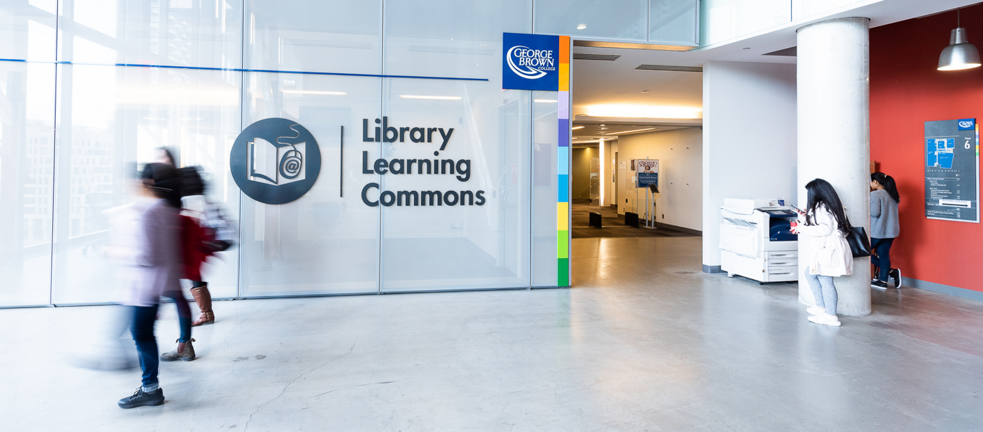 The entrance to the Waterfront LLC features a large translucent glass wall bearing the Library Learning Commons logo of a book and computer mouse with the @ on it. The GBC logo and colour-bar frames the doorway into the library. Several people walk by the entrance in motion blur, and a couple other students stand next to the printer outside the library.