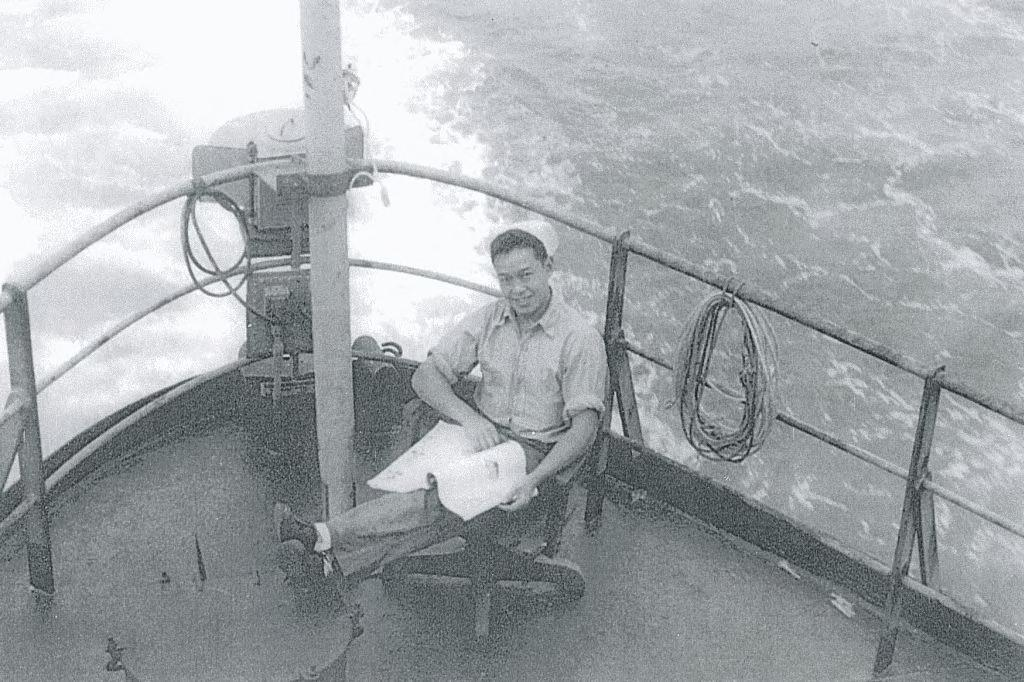 photograph of Andrew Wong reading on a ship at sea