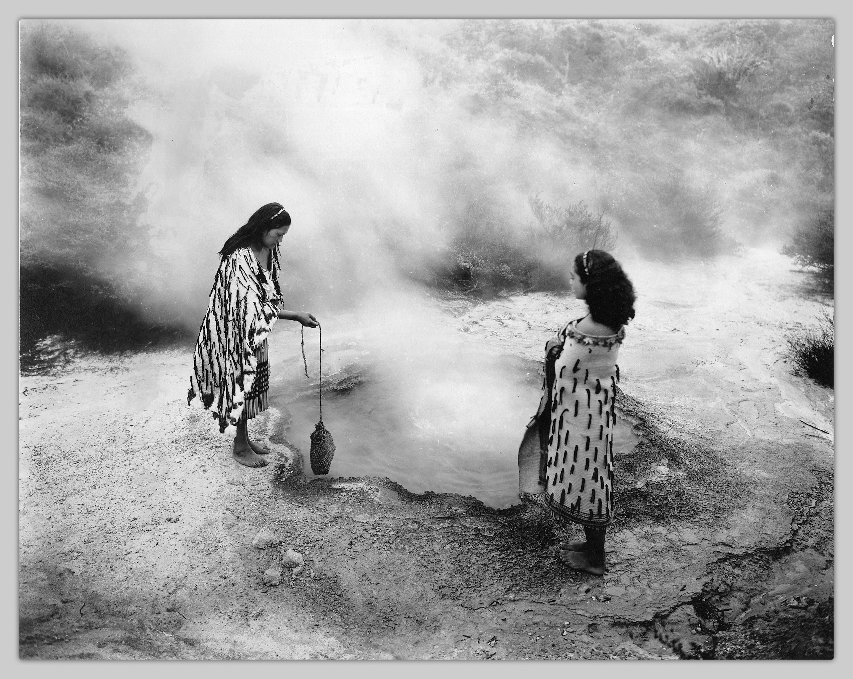 two Maori women cooking potatoes over a geyser