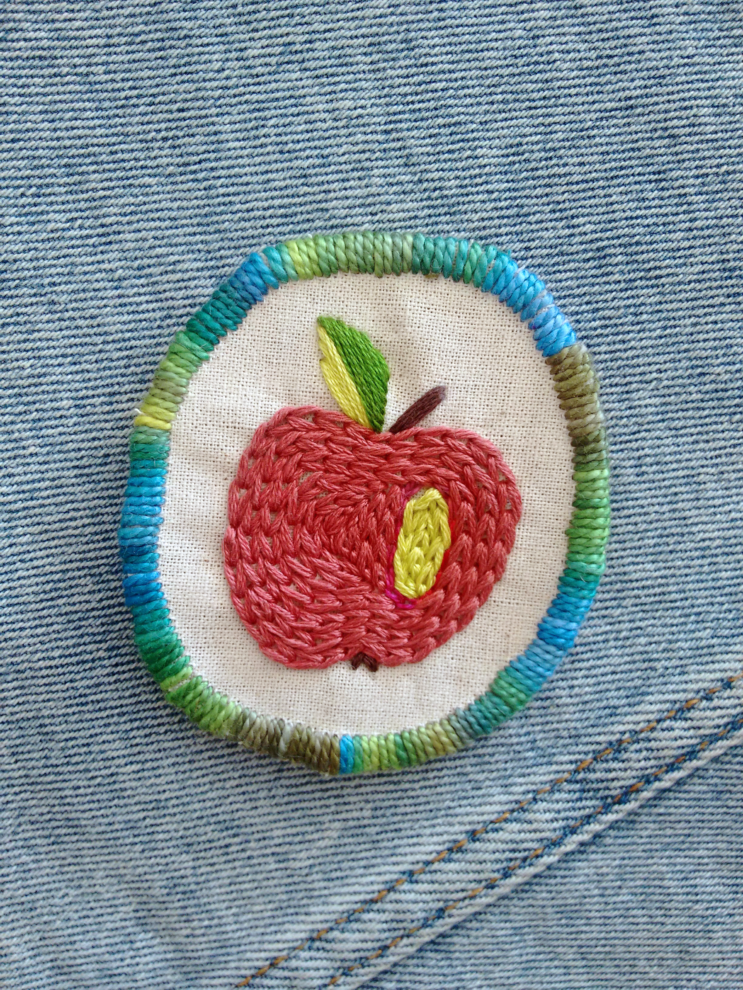 Embroidered apple patch with a blue green trim