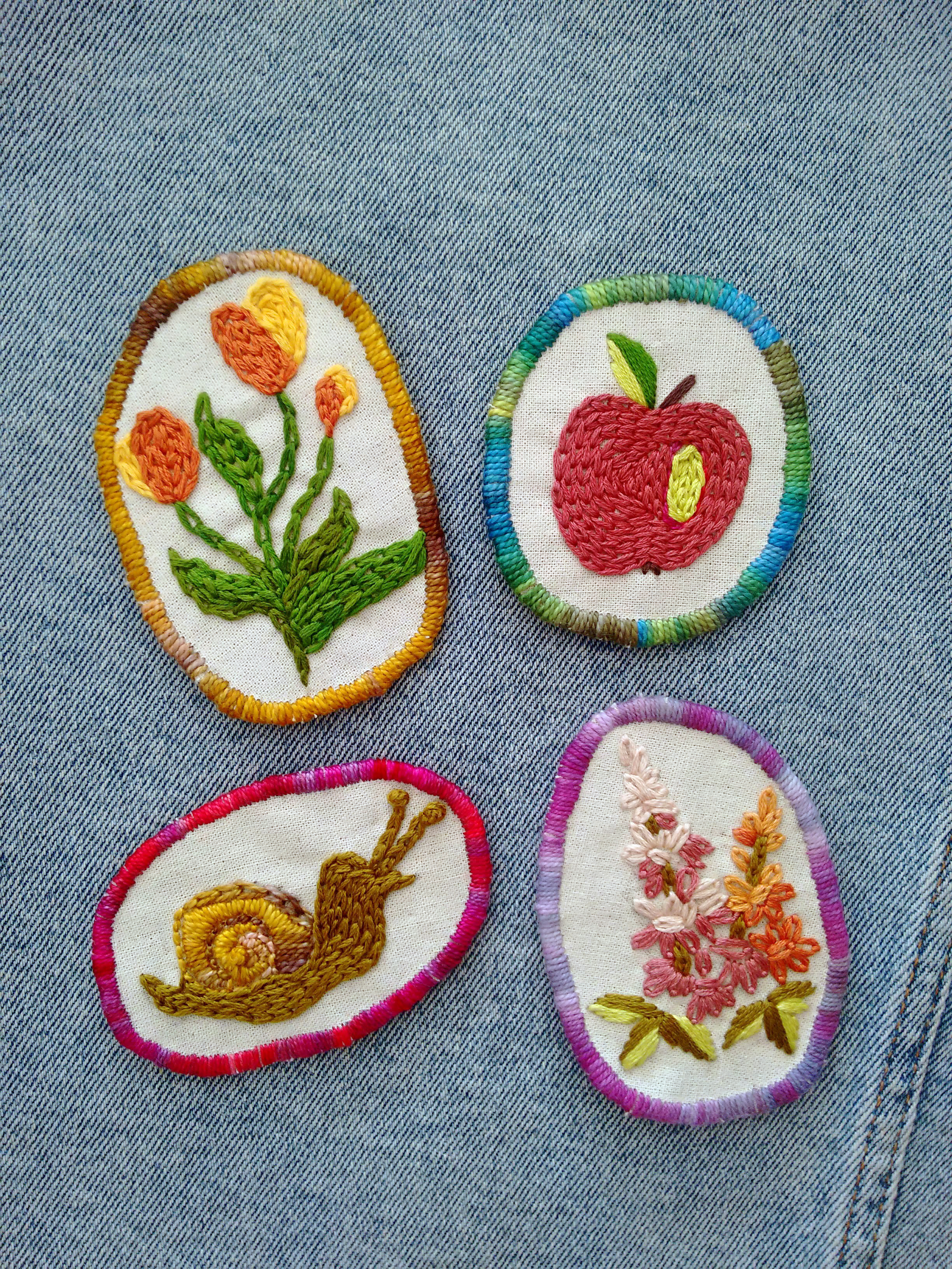 Four colorful patches on a jean background