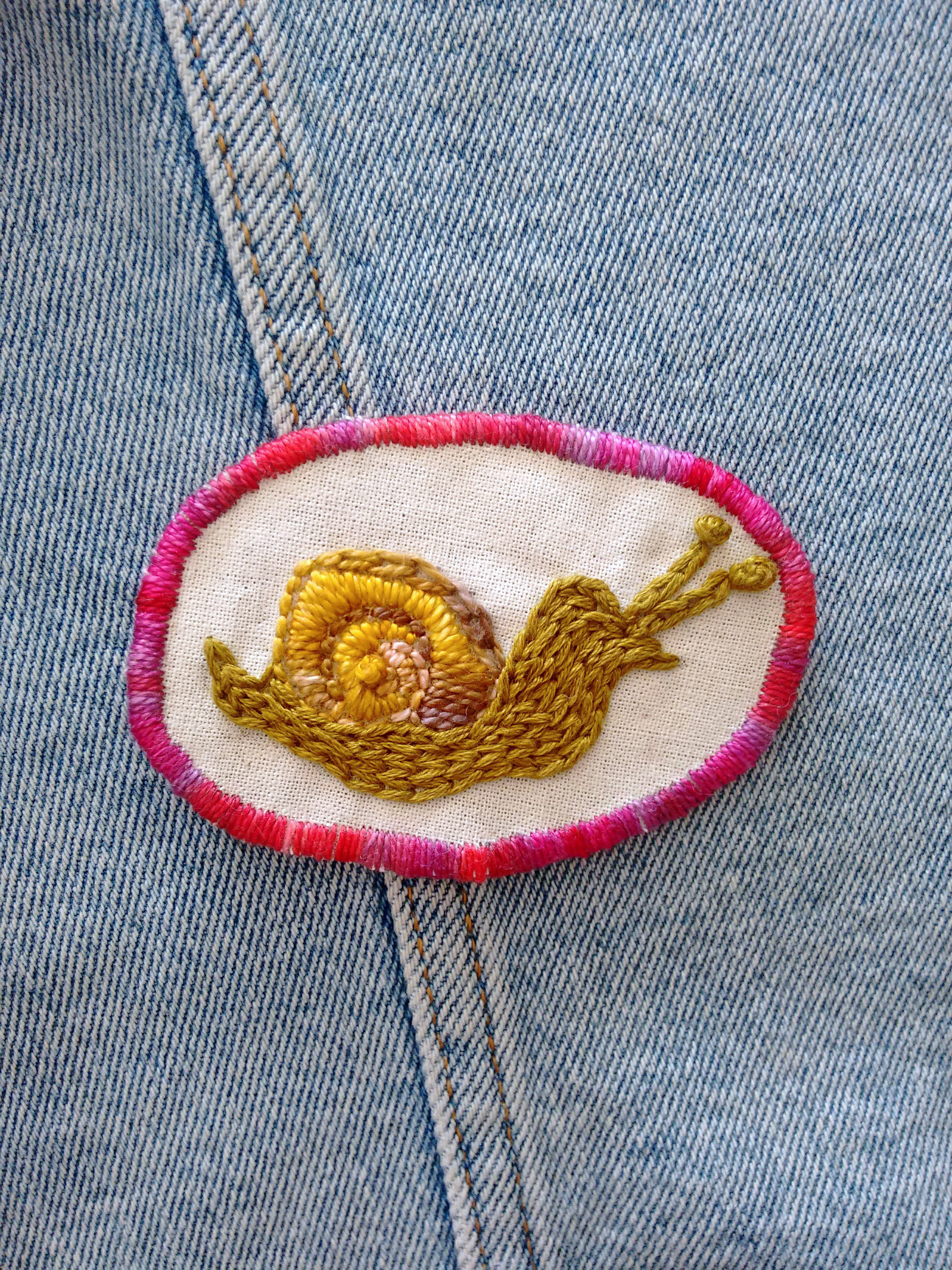 Embroidered snail patch with a red trim