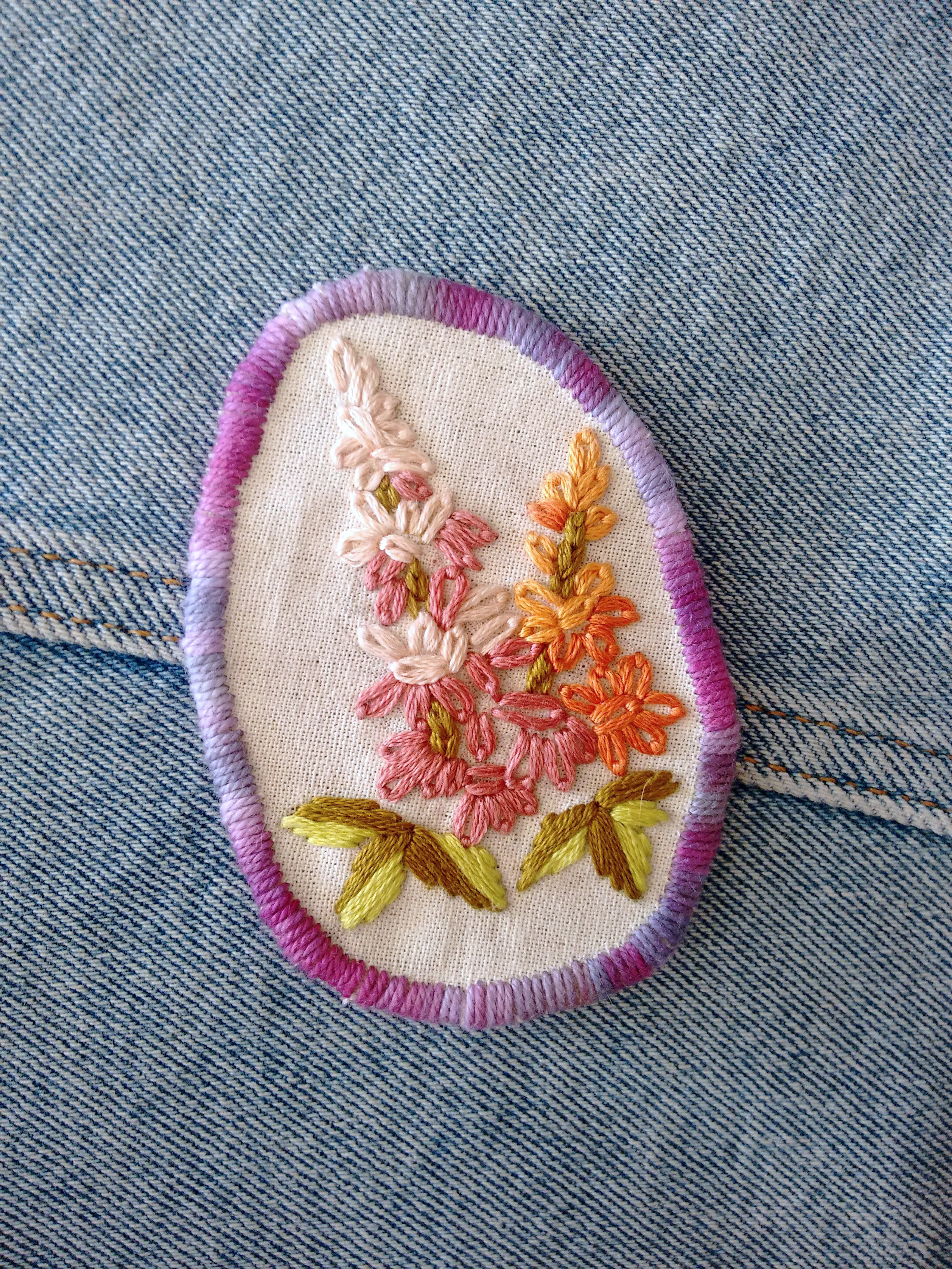 Embroidered snapdragon patch with a purple trim
