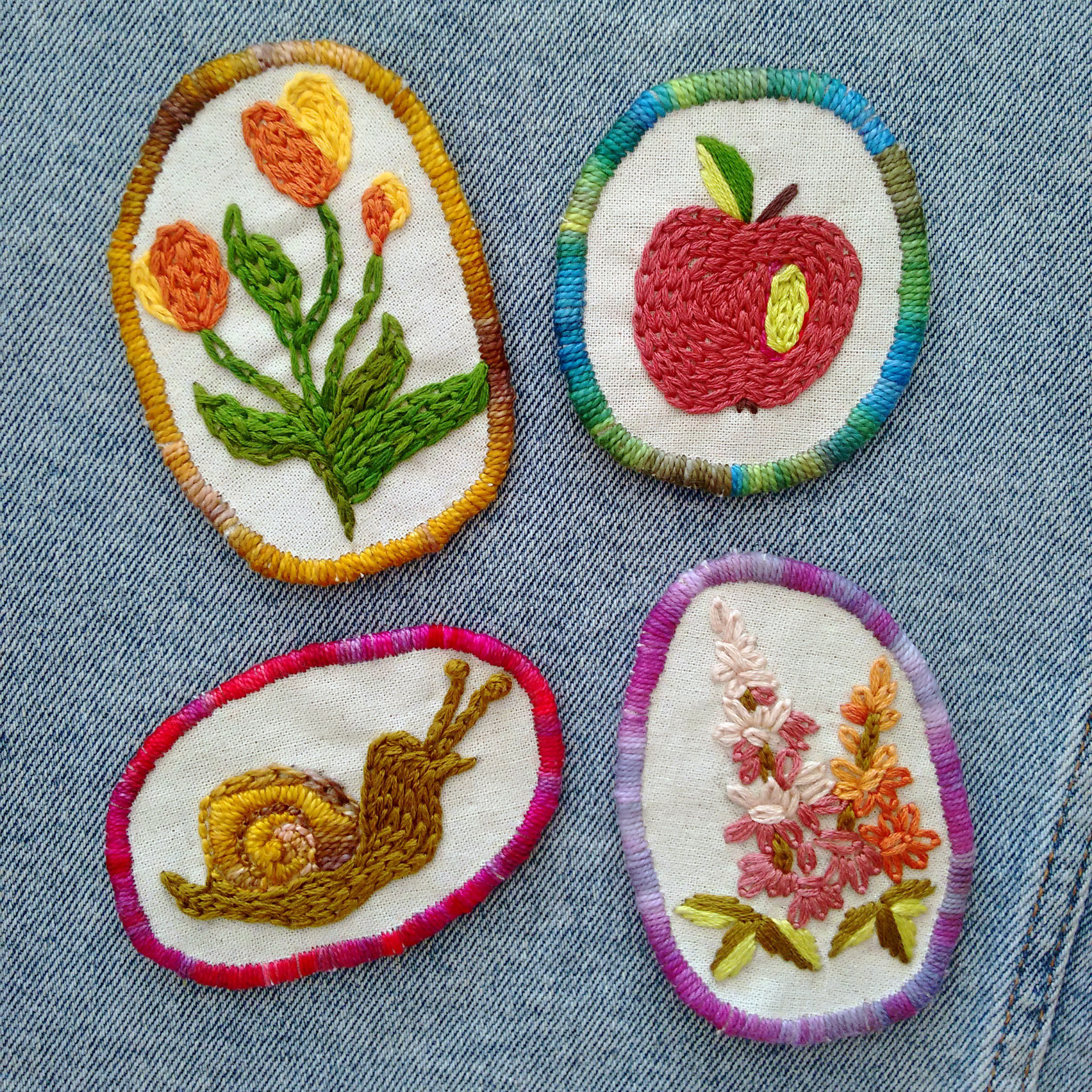 Four embroidered patches on a jean background