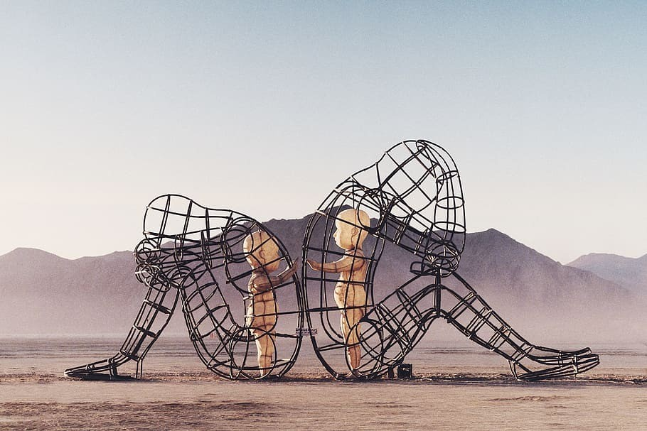 Burning Man Sculpture wire frame form of two people sitting on the ground back to back with small child sized human figures inside each wire sculpture reaching toward each other