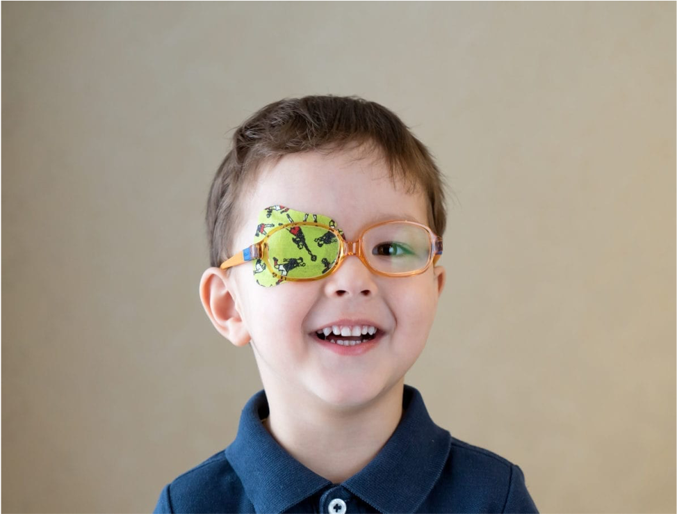 Smiling child wearing glasses and an eyepatch