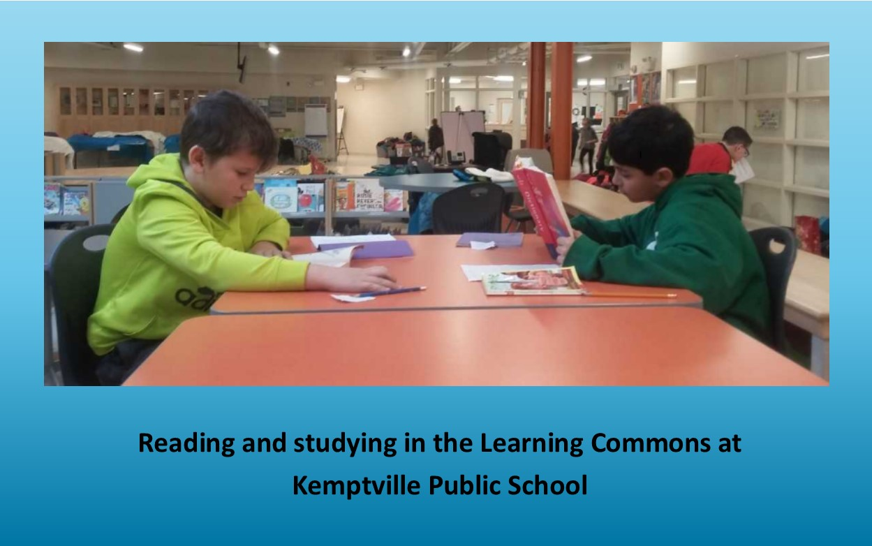 Two boys sitting and reading books at a table in the LC