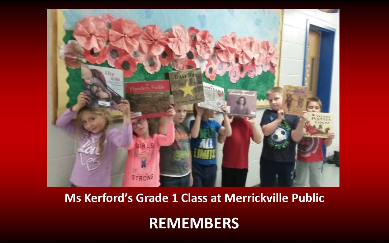Children in hallway in front of a Remembrance Day bulletin board.  The children are holding Remembrance Day books.
