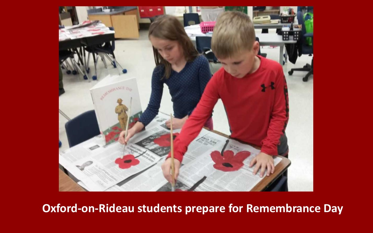 Two children painting poppies on newspaper