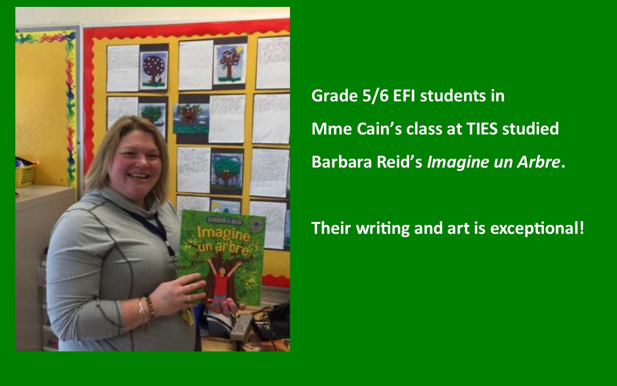 Photo of teacher holding Barbara Reid's book Imagine un arbre.  Student drawings and written work on bulletin board in the background.