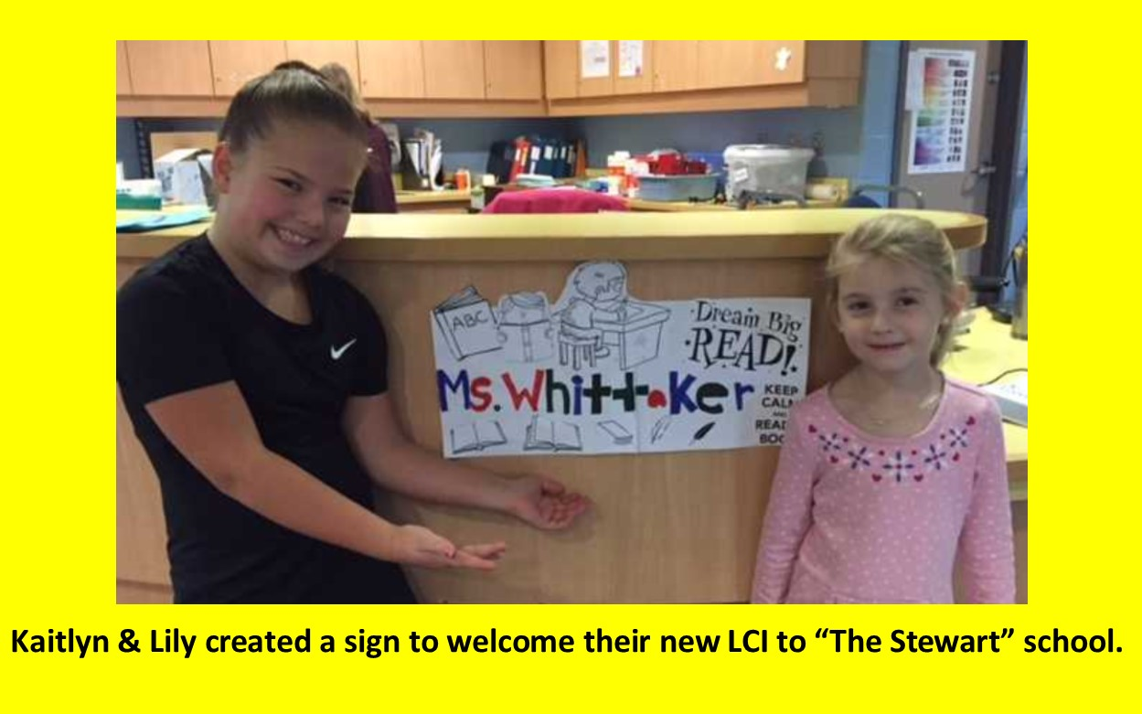 Kaitlyn and Lily in front of circulation desk displaying new LC sign for Ms. Whittaker