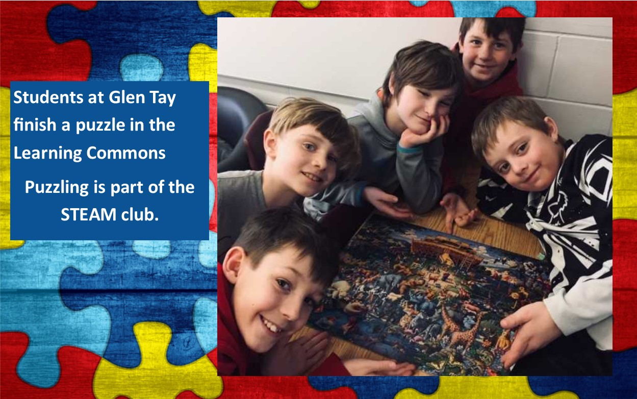 Five boys gathered around a puzzle that they have completed.