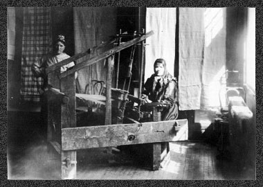 Mrs Bludoff, Sr., of Verigin, is seated at her loom which was brought from Russia [in 1898]. Mrs. Kosema Tarassoff of Langham stands beside her. Lengths of woollen homespun and linen hang on the back wall. (Special Collections Manuscripts Collection - MSS C555/1/4.2e/1)
