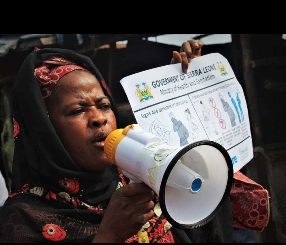 Kaddy Mansaray, Chair, Funkia [Sierra Leone] Market Women's Association provides COVID prevention information with a poster and megaphone