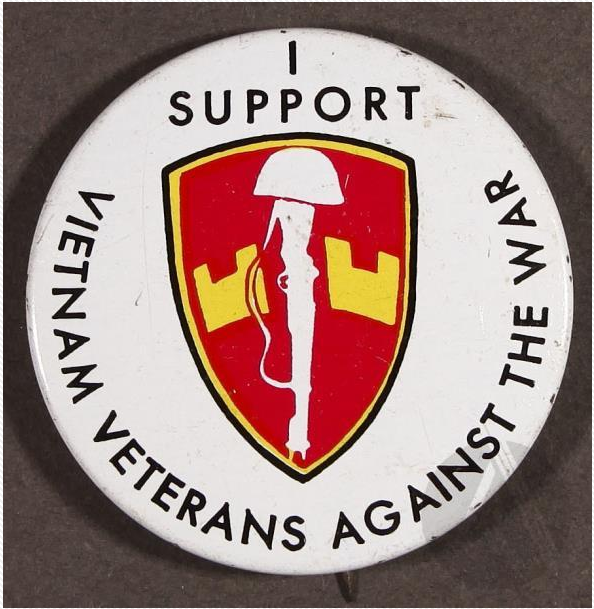 "Lapel pin from circa 1971 with the phrase: ""I support Vietnam Veterans Against the War"" and an insignia showing a rifle and helmet."