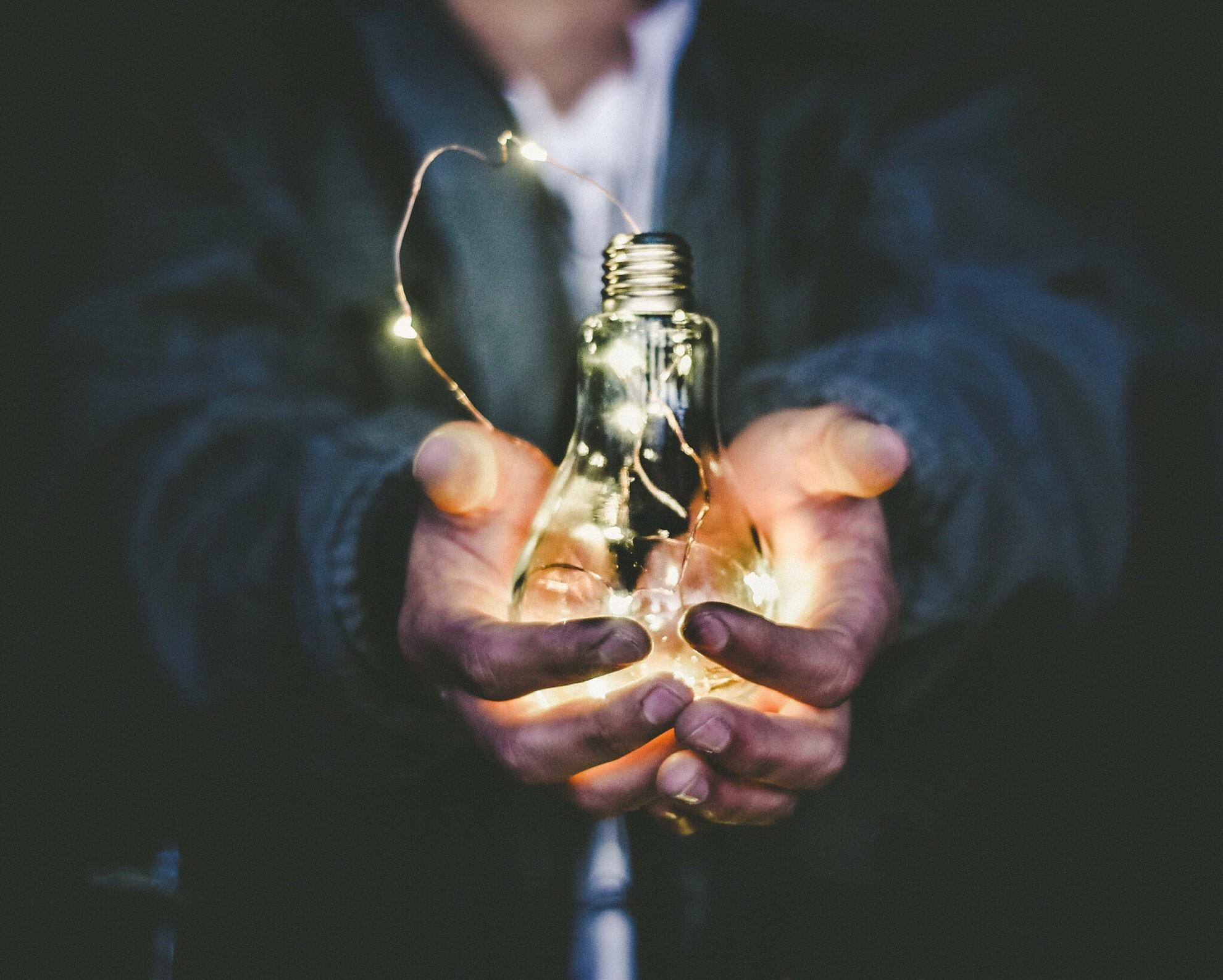 man holding incandescent bulb photo