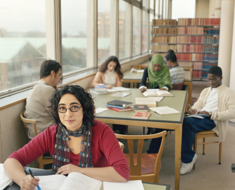A library with several students studying around tables