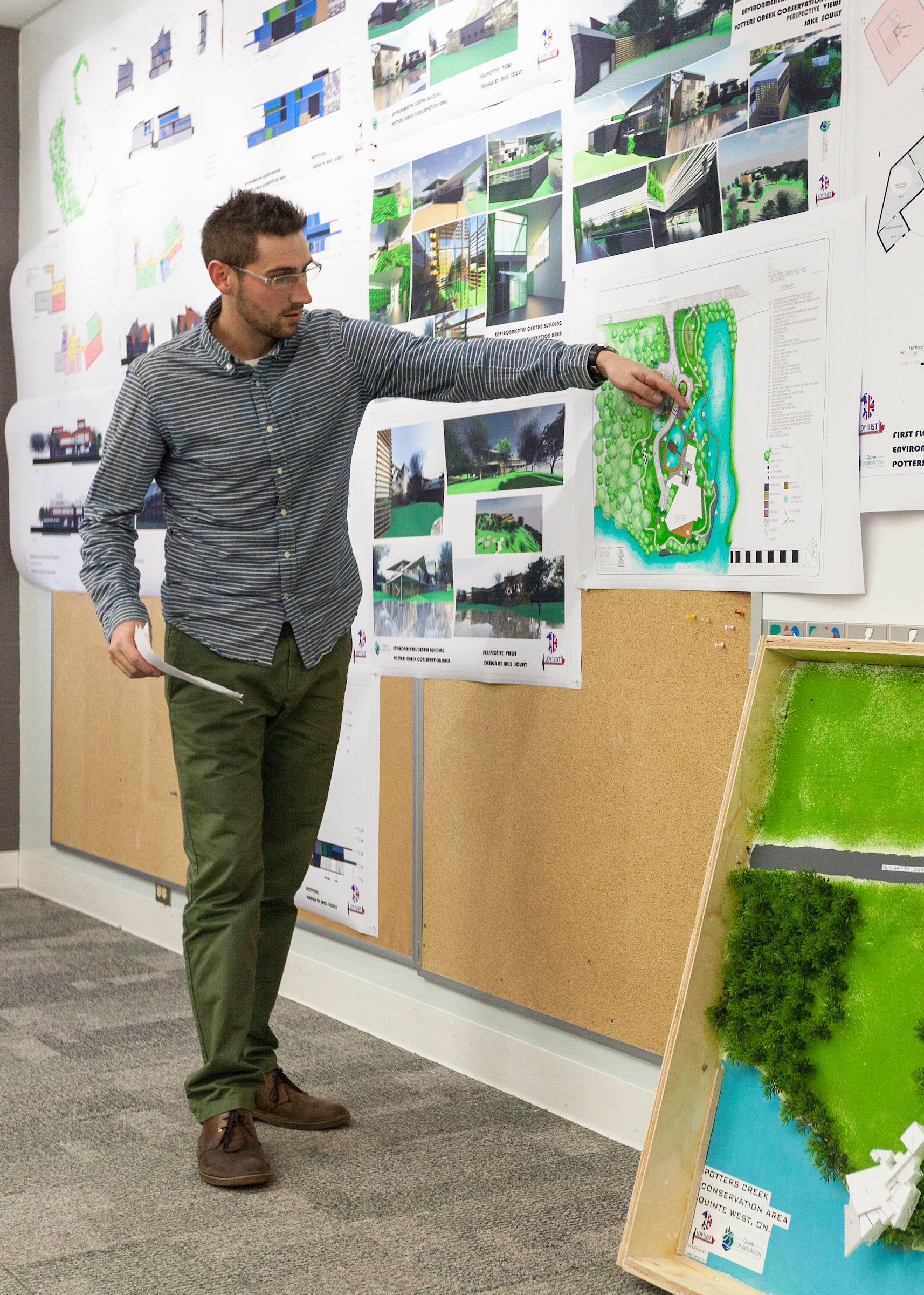 Architectural Technician student Jake Scully stands at the front of a classroom to presents a design study. He is pointing out features on architectural drawings.