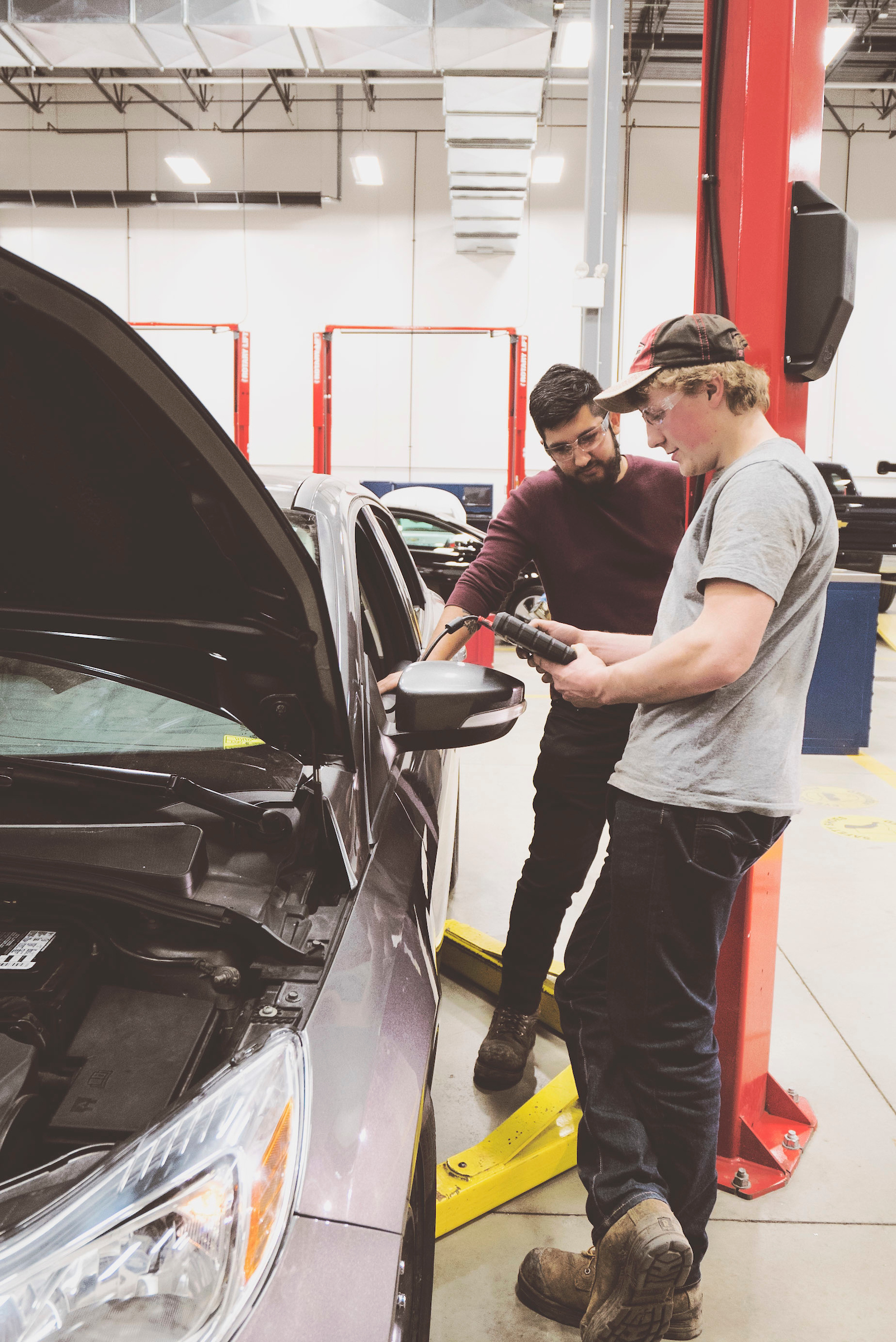 Two students stand beside a car in an auto shop. They are looking at a hand-held computer connected to the car.