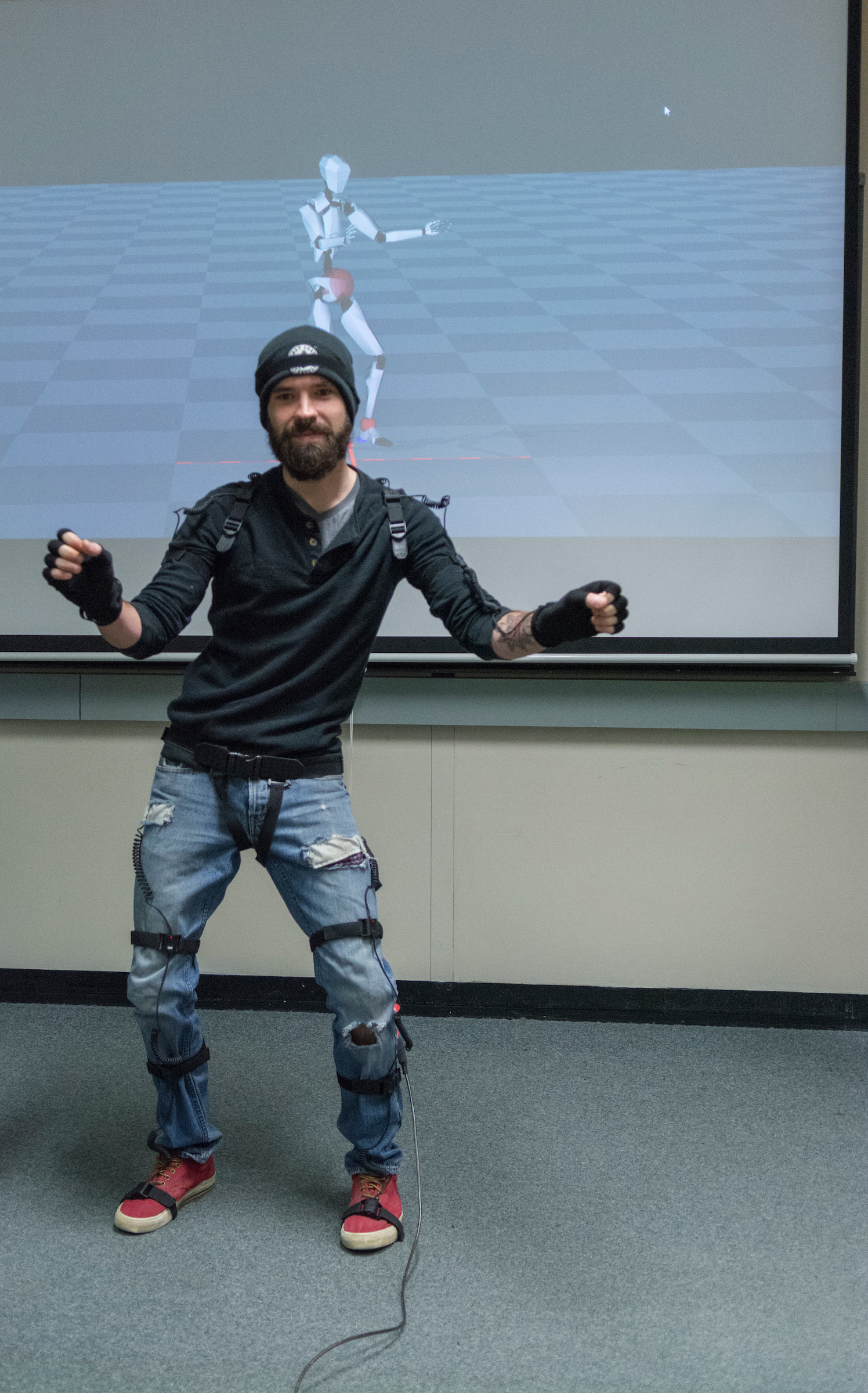 An animator wears motion capture equipment. The screen behind him displays a simple figure making the same movements.