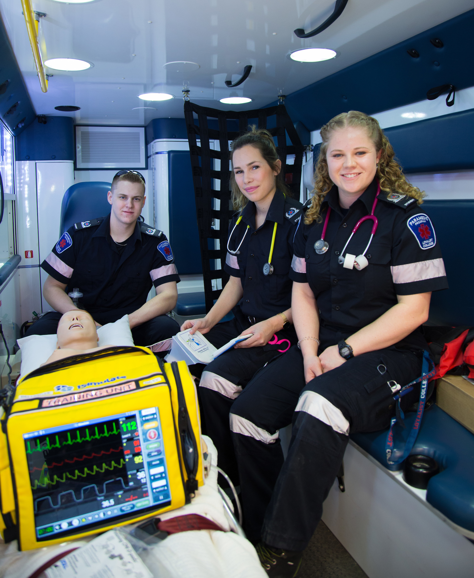 Three paramedics pose in the back of an ambulance beside a stretcher that holds their equipment.