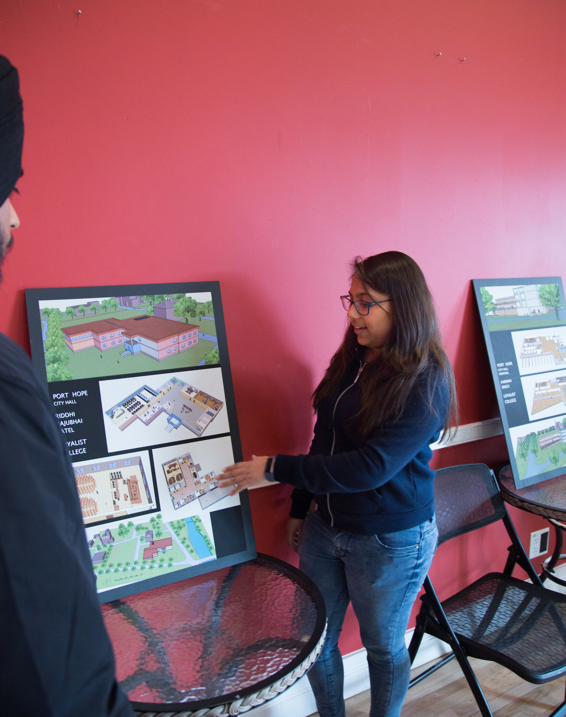 A student in a dark blue sweater and jeans points out features in her architectural drawings. The drawings show landscapes and structures.