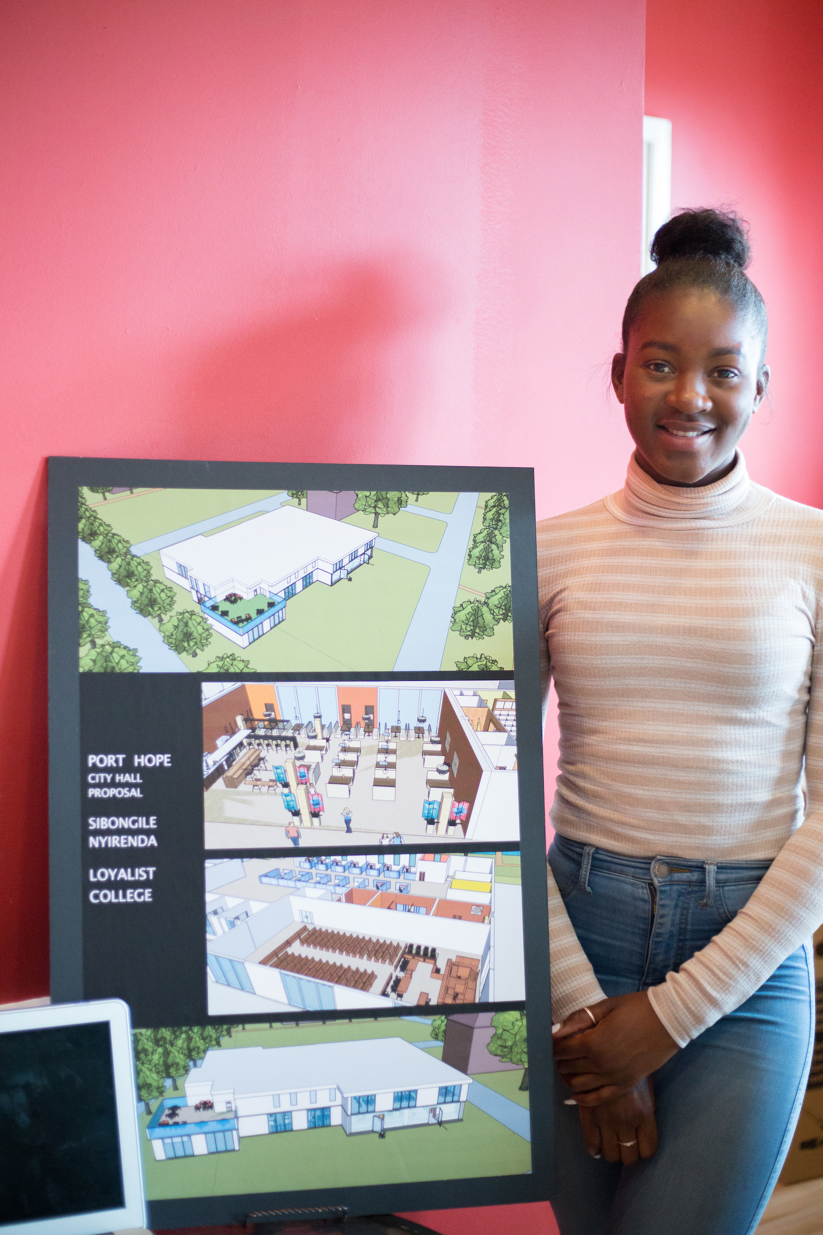 A student in a white sweater and jeans stands in front of her architectural drawings. The drawings show landscapes and structures.