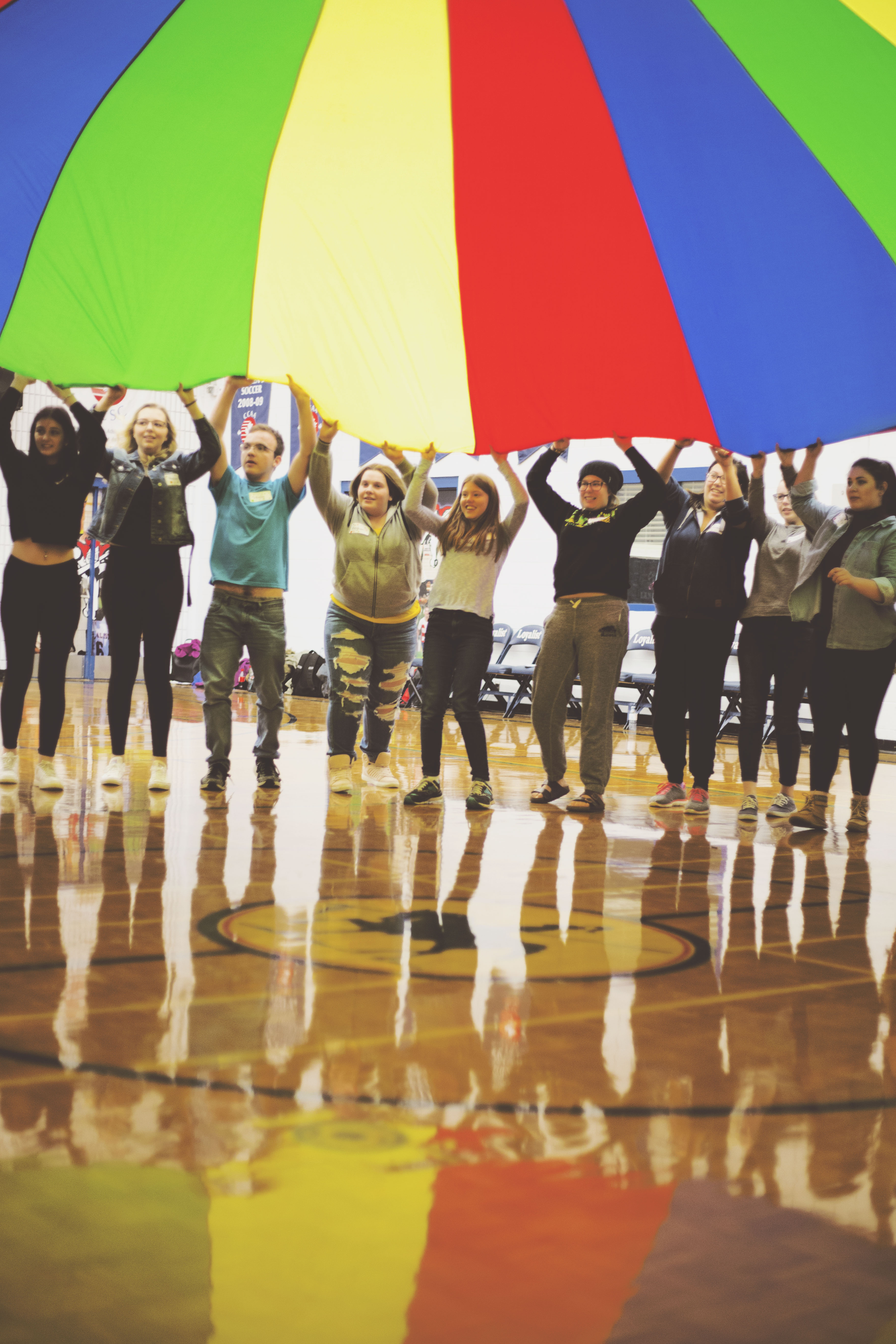 A group of students play with a large multi-coloured parachute in a gymnasium.
