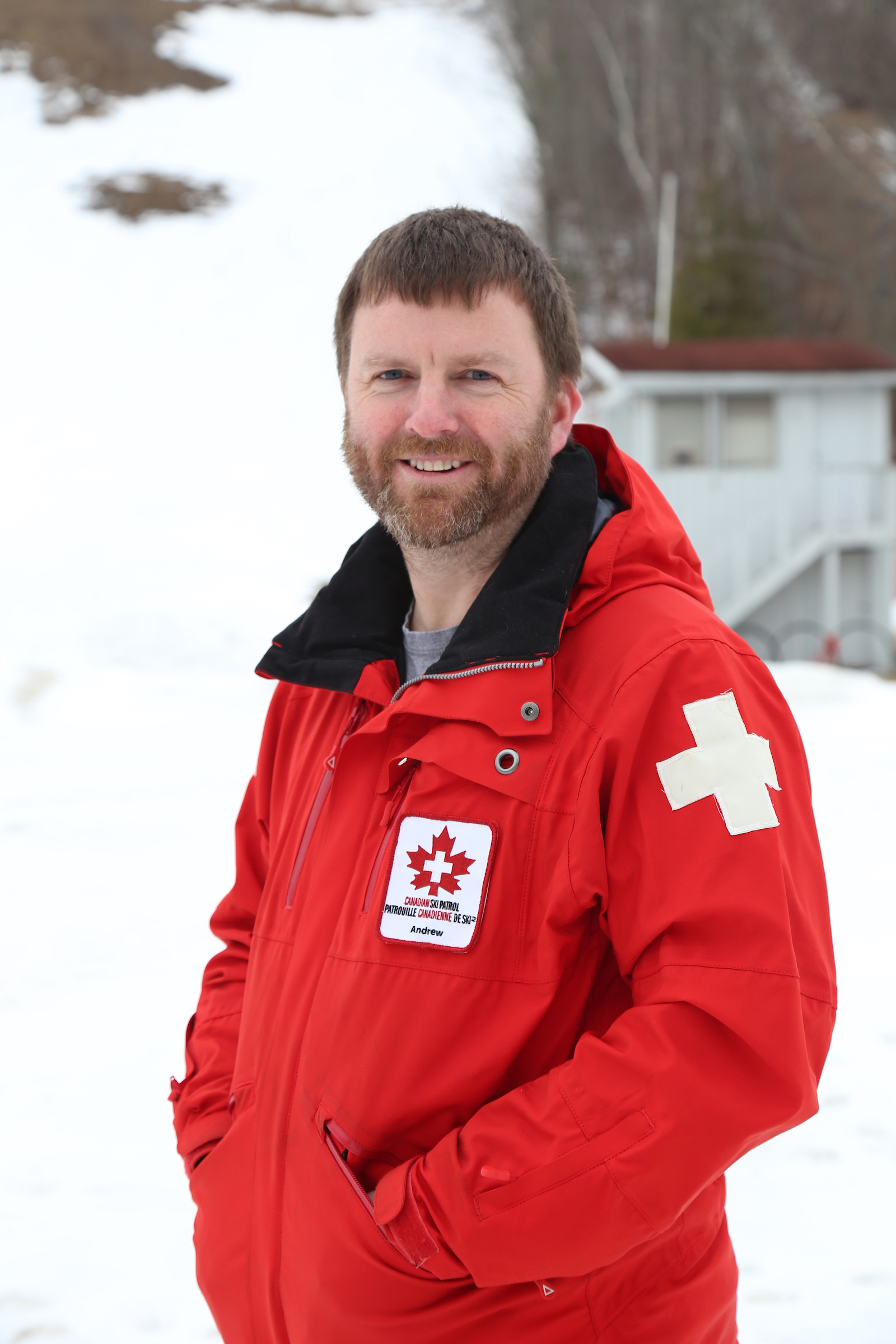 A ski patrol staff member poses in front of a snowy ski hill wearing a red parka with medical insignia. He smiles at the camera.