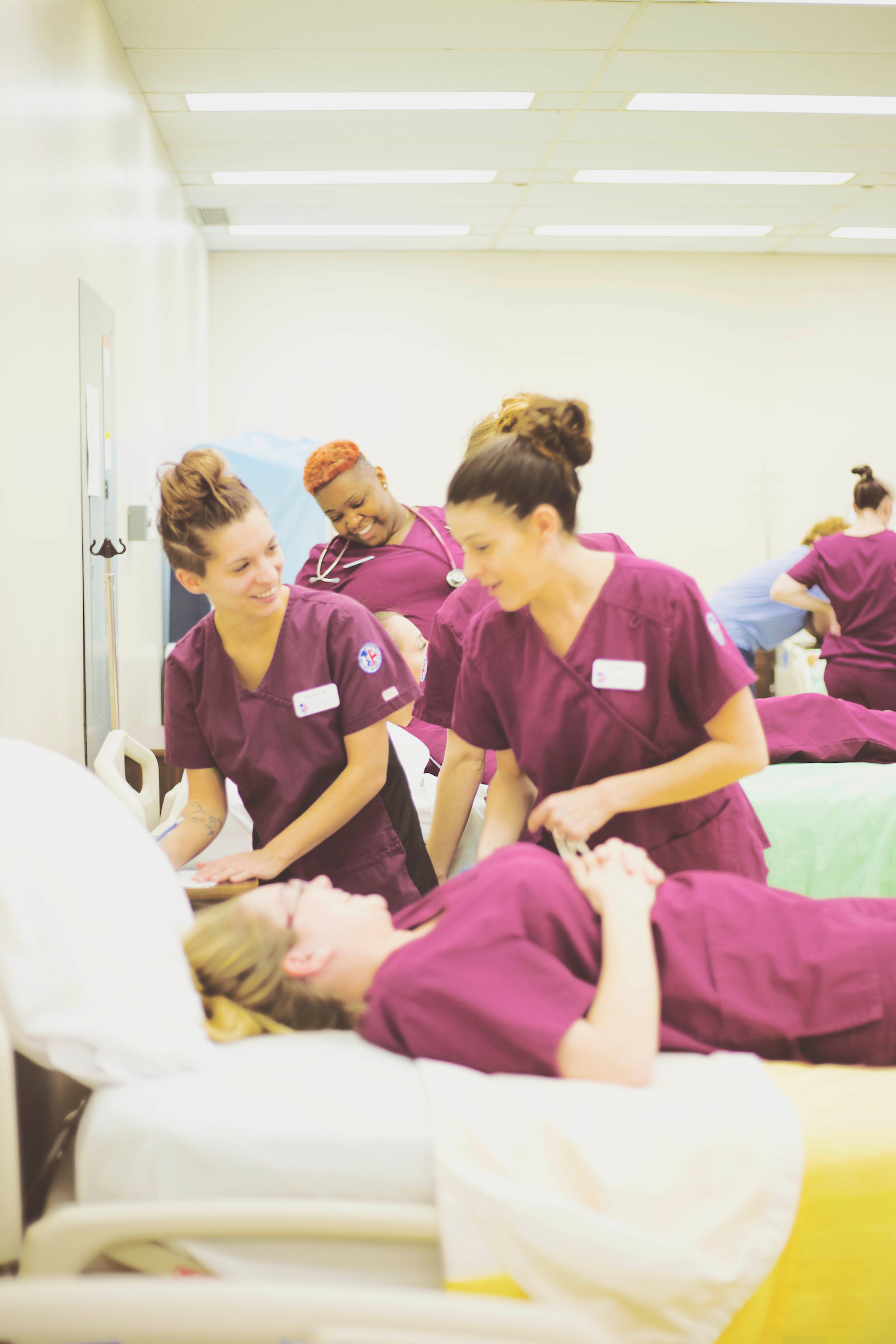 Personal support worker students work through a simulation in class. One student plays the patient and lays in bed, which the others act as PSWs and assist her.