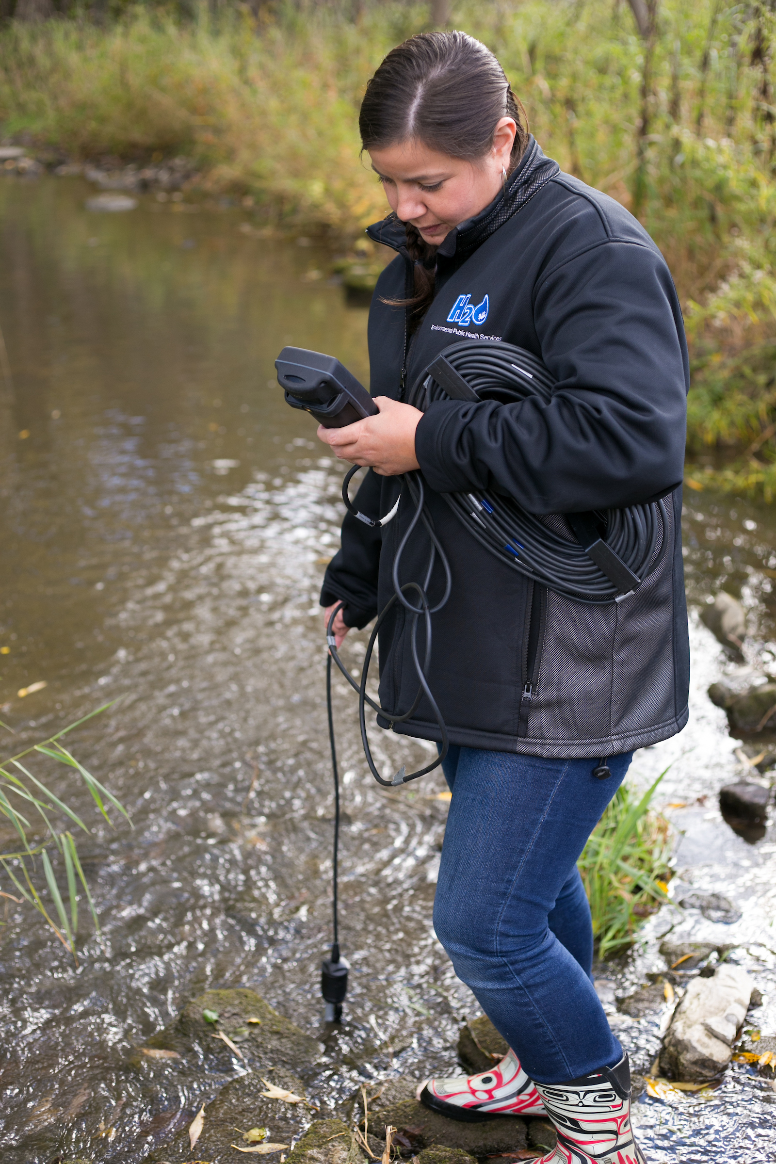 A scientist stands in a stream, and takes readings using a piece of electronic equipment.
