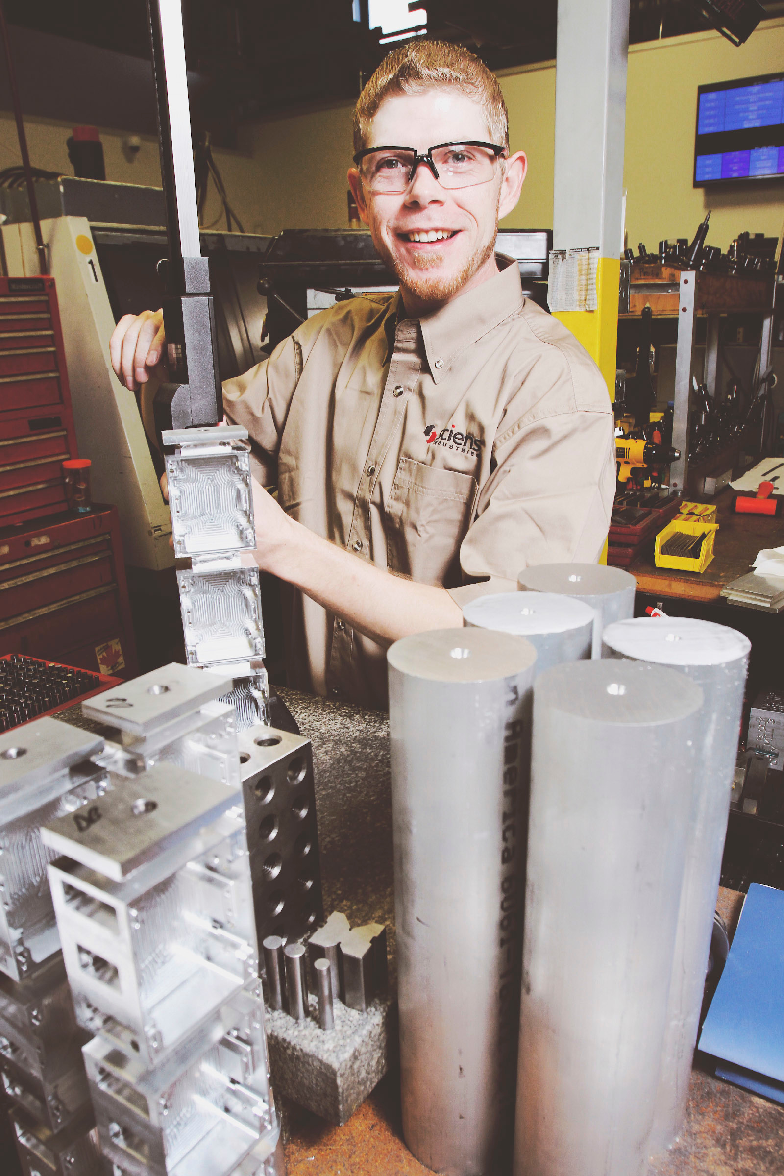 A machinist works on a piece of equipment in a workshop. He pauses in his work and smiles at the camera.