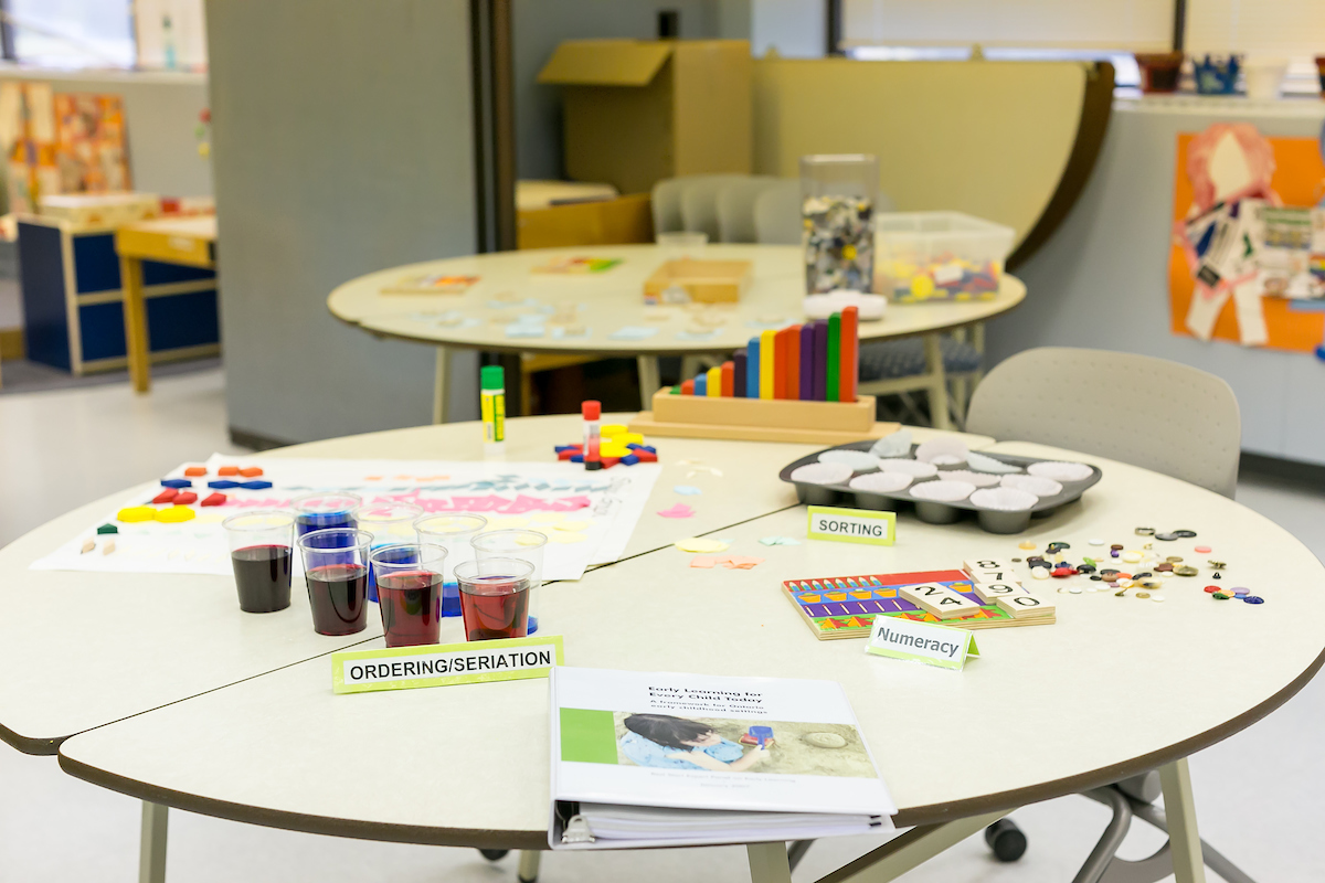A table in a pre-school classroom is set with craft supplies, ready for an activity.