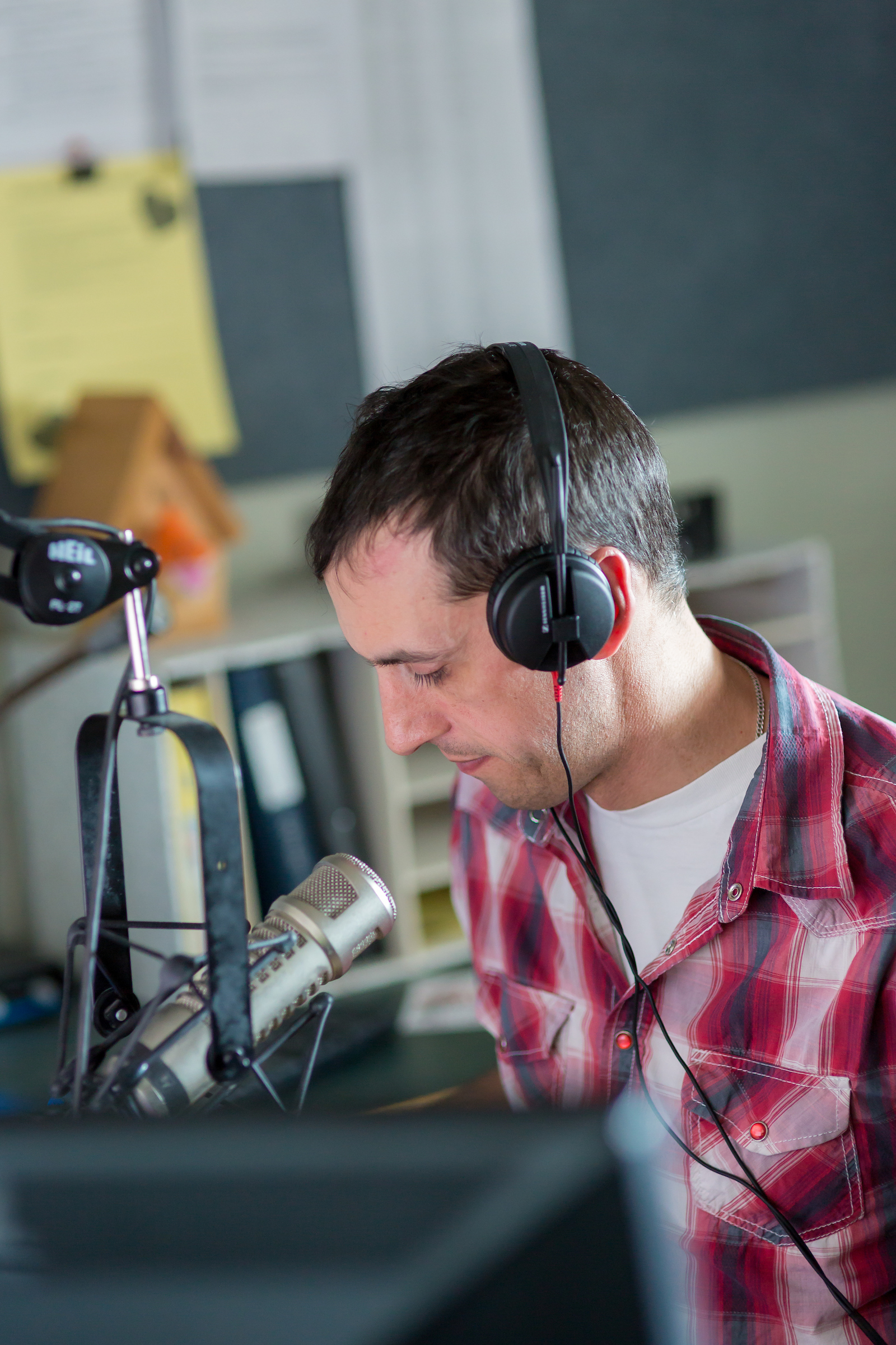 A radio host works in a sound booth. He wears headphones and sits in front of a microphone.