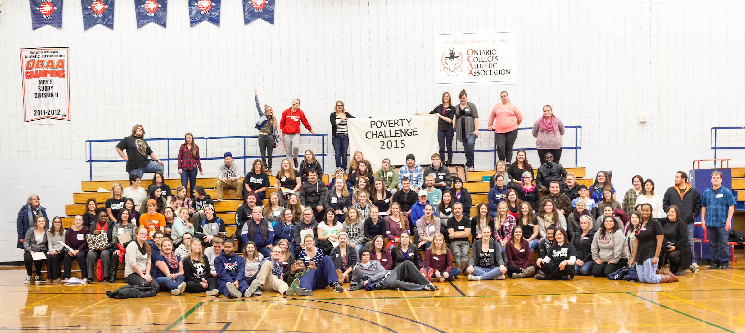 A large group of students pose for a photo in a gymnasium. A sign behind them reads,