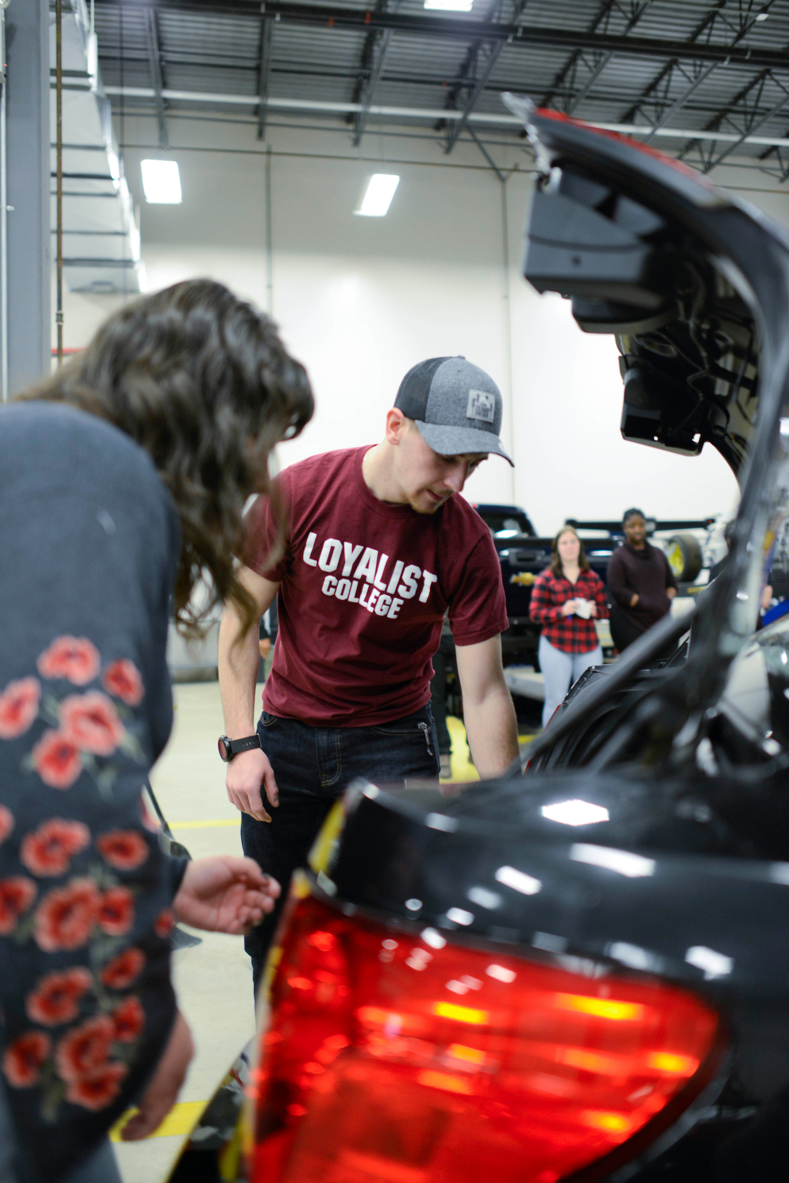 A group of Customs and Border Security students inspect the trunk of a car during a class exercise.