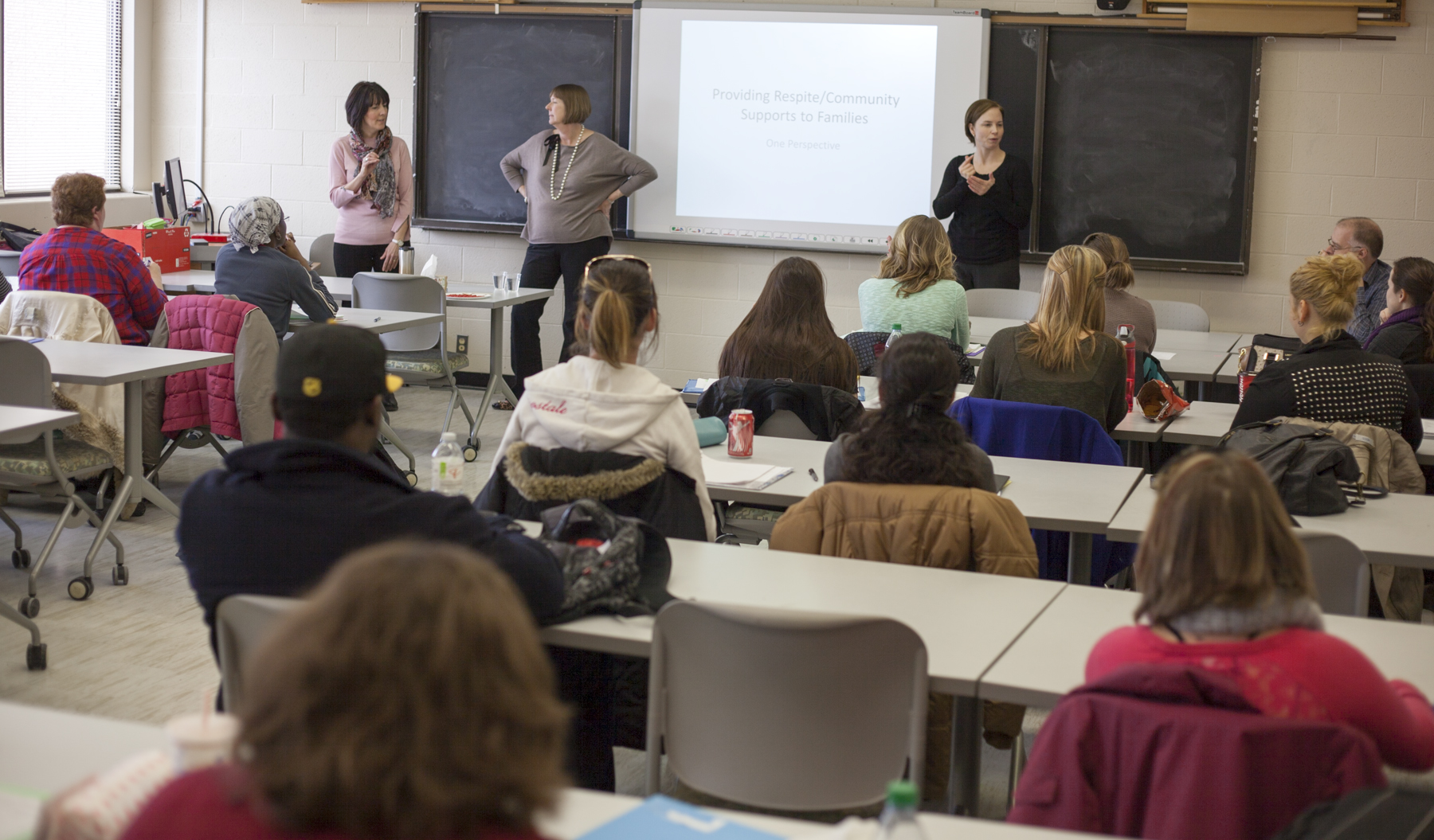 A group of students sit in a classroom and listen to two instructors, who stand at the front of the room. A sign language translator stands to the right side.
