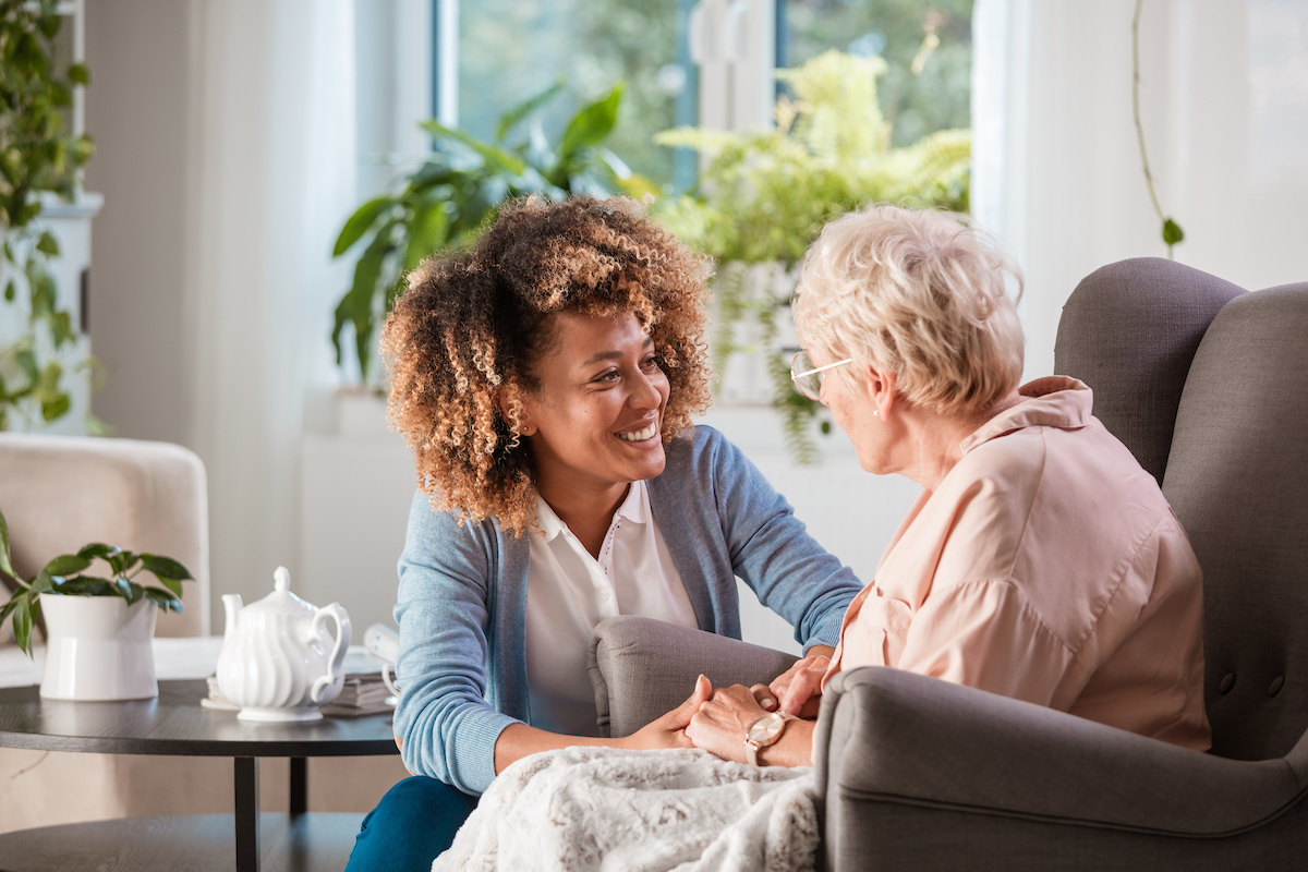 A young caregiver visits with an elderly client. They smile at each other.