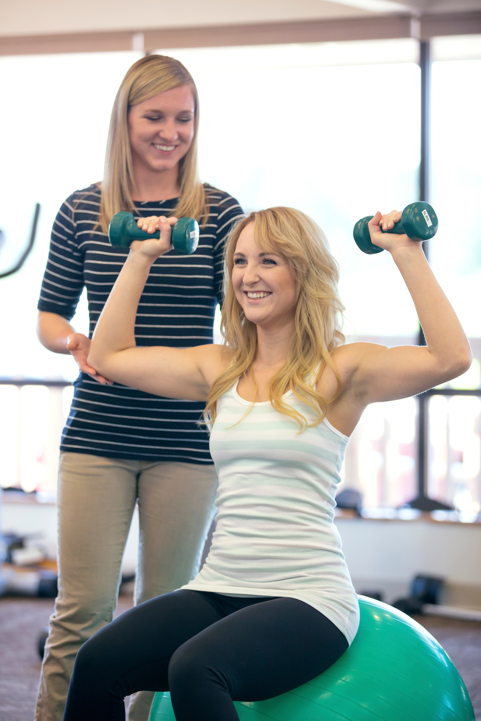A physical therapist helps a young female patient with an exercise using weights.