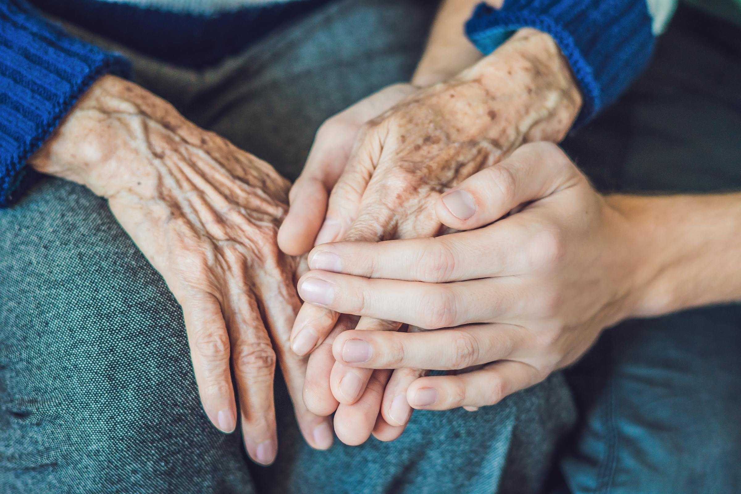 A young caregiver's hands hold the hands of an elderly client.