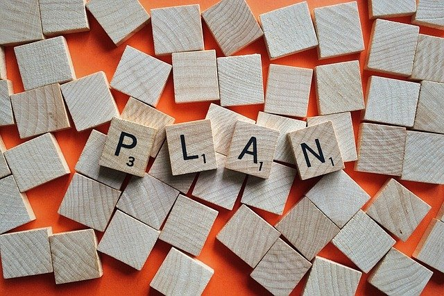 Square wooden tiles that spell the word plan