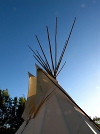 Photograph of a tipi, with blue sky and trees in the background.