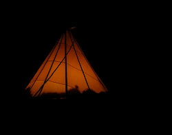 Photograph of a tipi at night, lit from the inside by firelight.