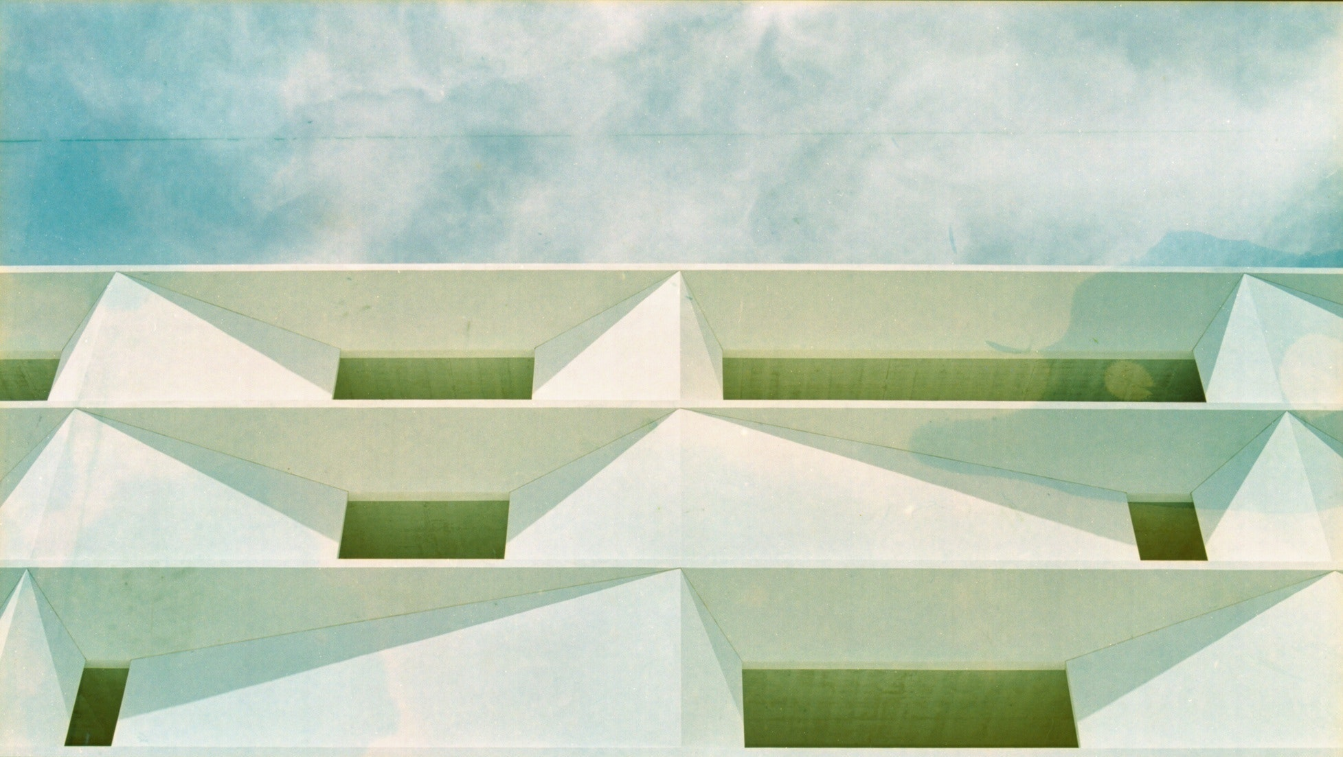 Portion of a facade of a contemporary building under a blue sky and clouds