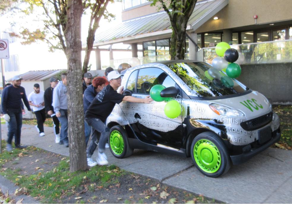 Students push a silver Smart Car up the Glen Drive sidewalk