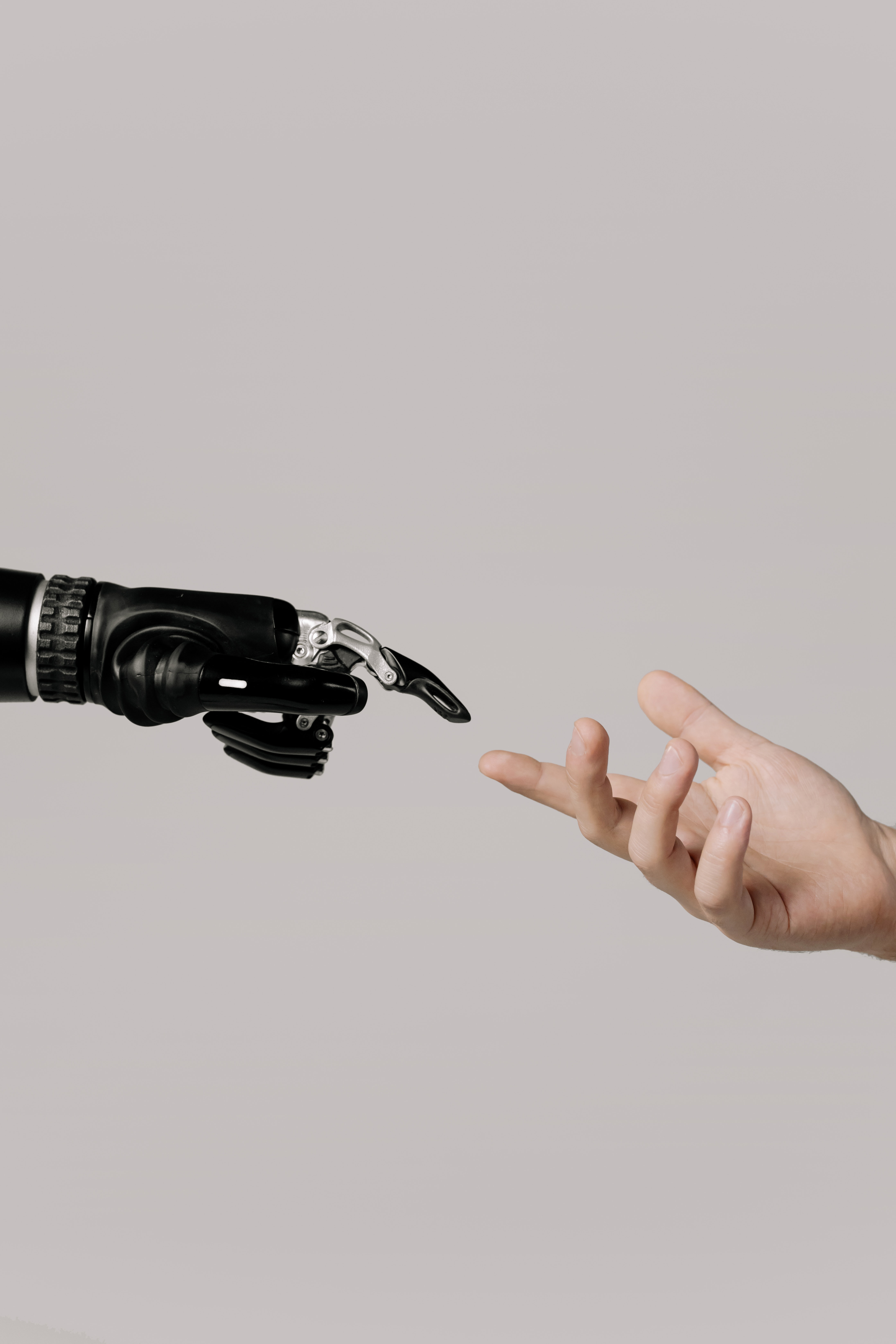 Cyborg hand and human hand almost touching