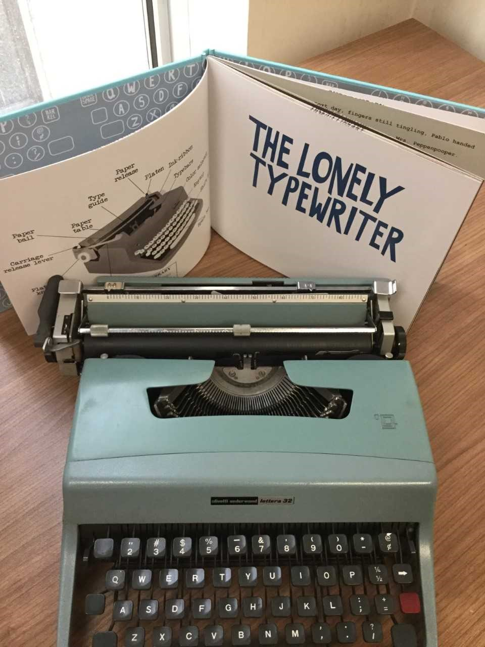 typewriter with open book behind it