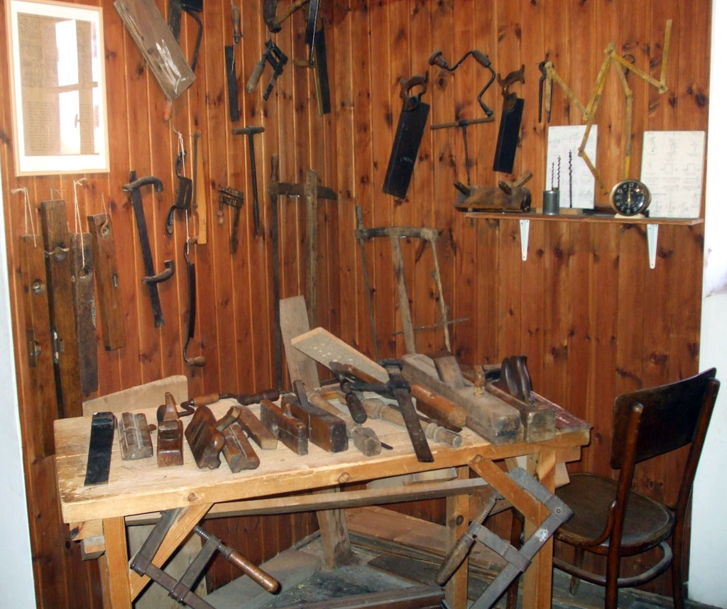 A workshop with numerous carpentry hand tools on a table and hanging on the walls.