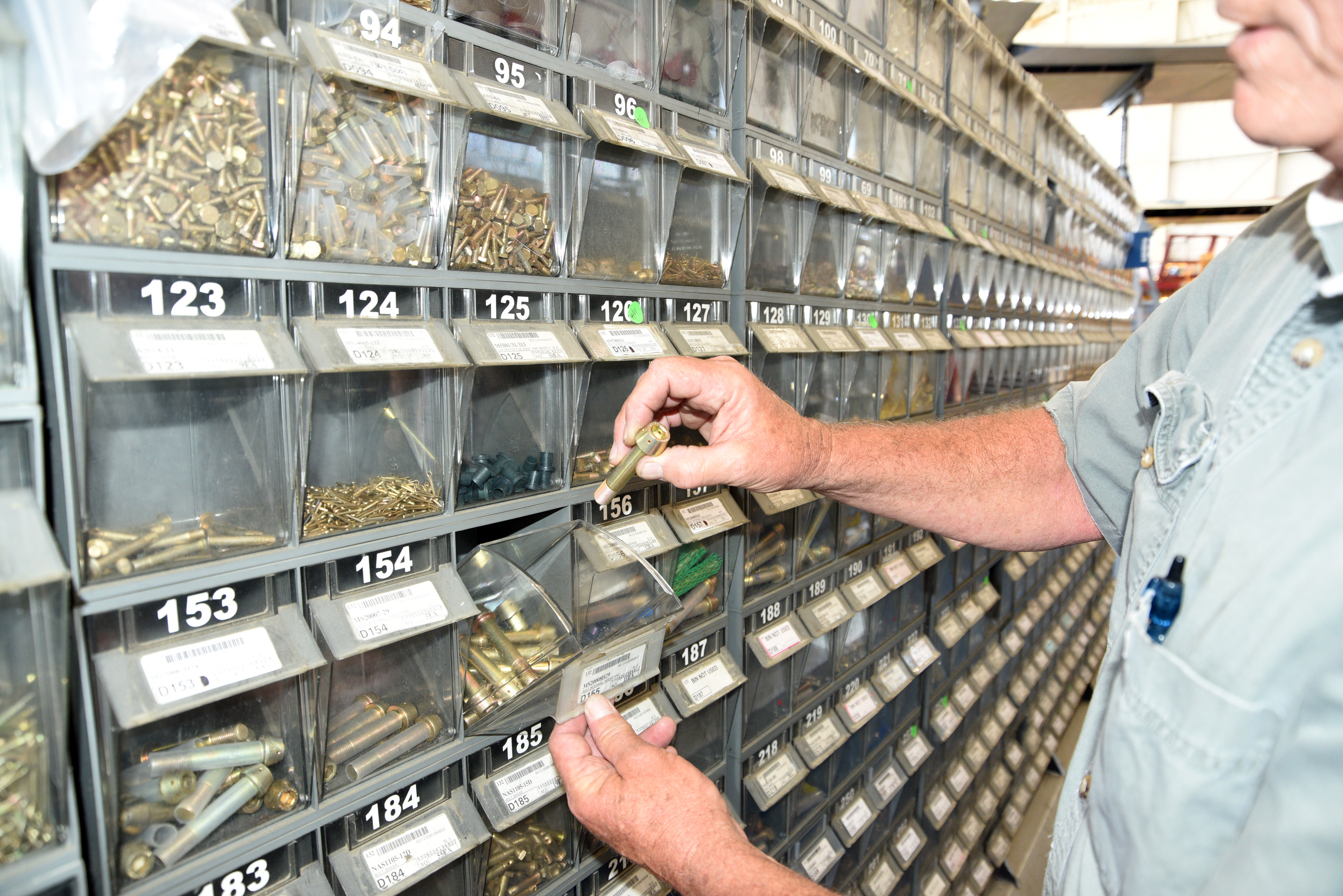 Parts and materials worker browses shelving containing various supplies.